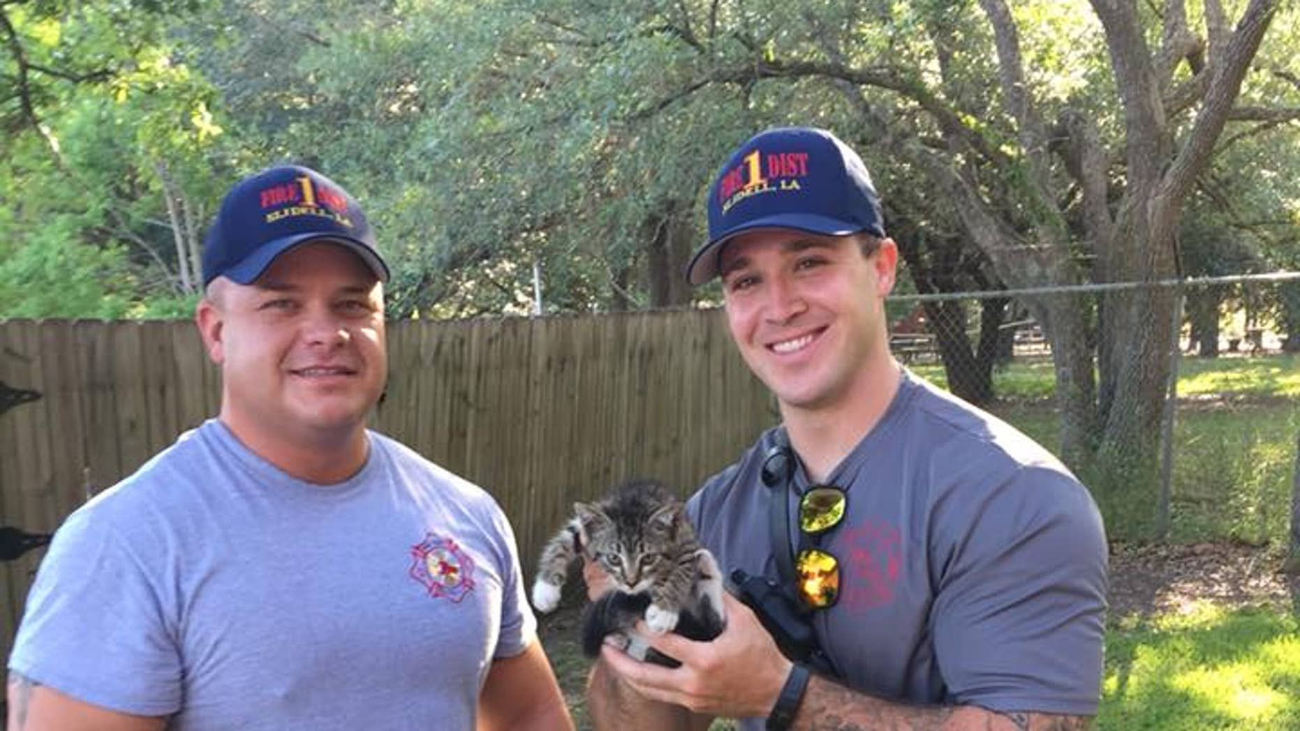 """Firefighters Eric Dupuy (right) and Richie Carter (left) """"performed a kitten extrication,"""" according to St. Tammany Fire Protection District #1."""
