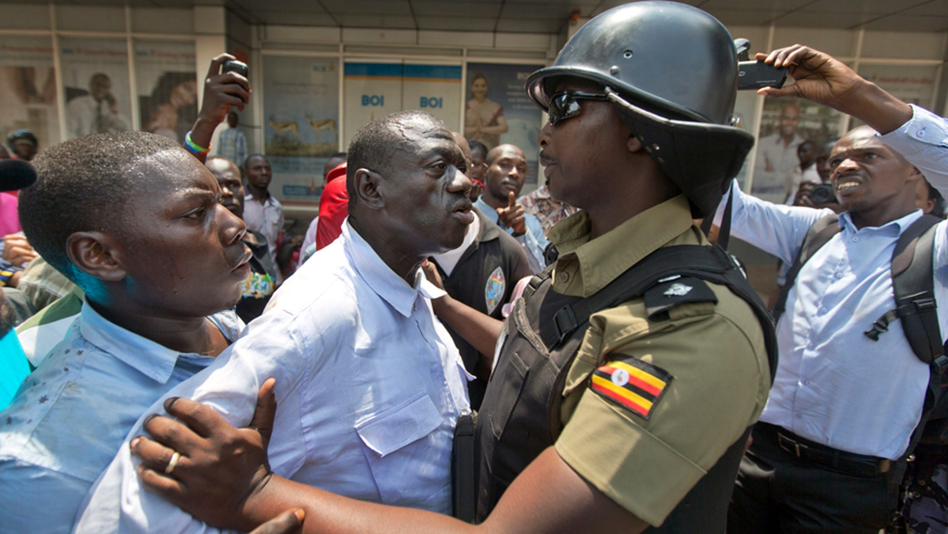 Feb. 15, 2016: Leading opposition leader and presidential candidate Kizza Besigye, center, is grabbed before being arrested by riot police in downtown Kampala, Uganda.