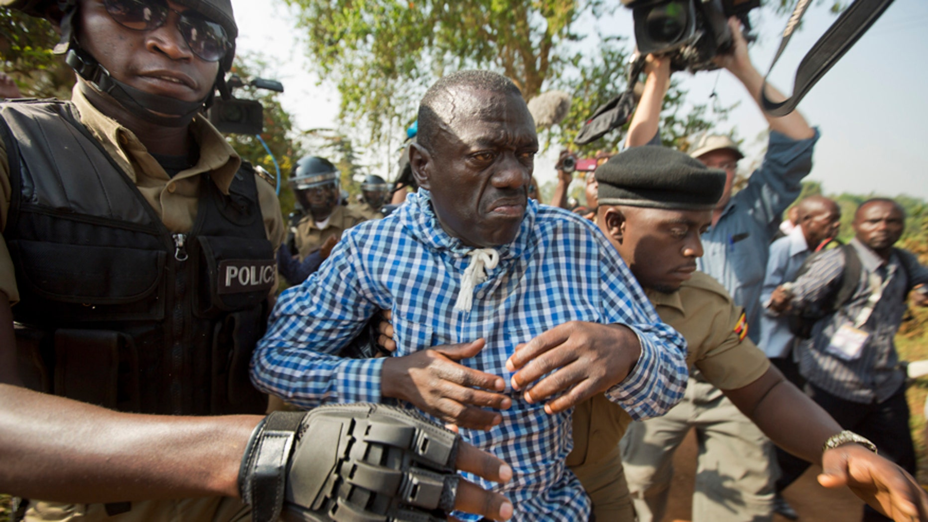 Feb. 22, 2016: Uganda's main opposition leader Kizza Besigye, center, is arrested by police and thrown into the back of a blacked-out police van which whisked him away and was later seen at a rural police station, outside his home in Kasangati, Uganda.