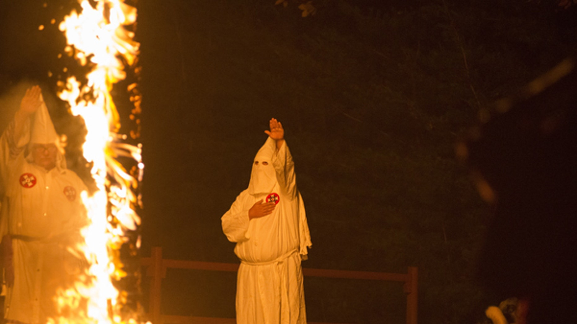 A member of the Ku Klux Klan salutes a lit cross during a cross lighting ceremony at a private residence in Henry County, Virginia, October 11, 2014. The Ku Klux Klan, which had about 6 million members in the 1920s, now has some 2,000 to 3,000 members nationally in about 72 chapters, or klaverns, according to the Southern Poverty Law Center, an organization that monitors extremist groups.  REUTERS/Johnny Milano