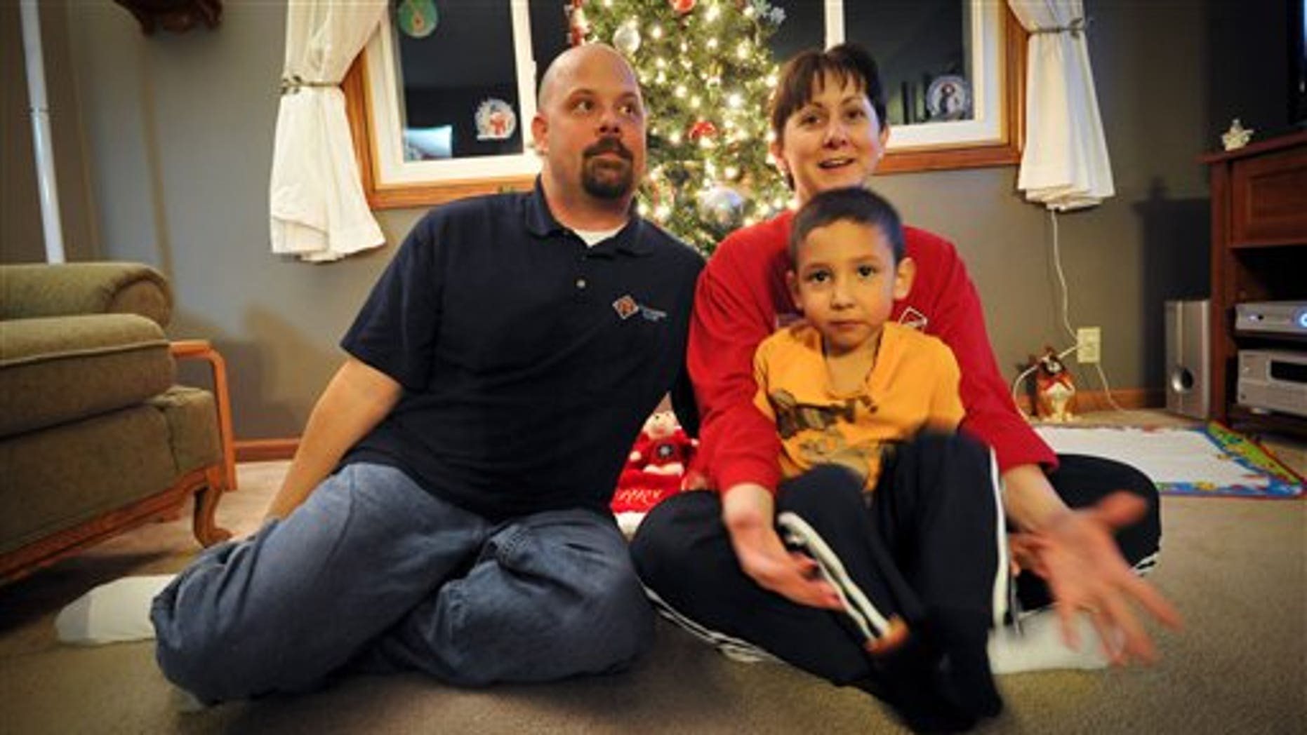Dec. 15: Dona, Matt, left, and Bryce Bremser, sit for photos at their Omaha, Neb., home. The Bremsers had their layaway at Kmart paid off by an unknown good Samaritan.