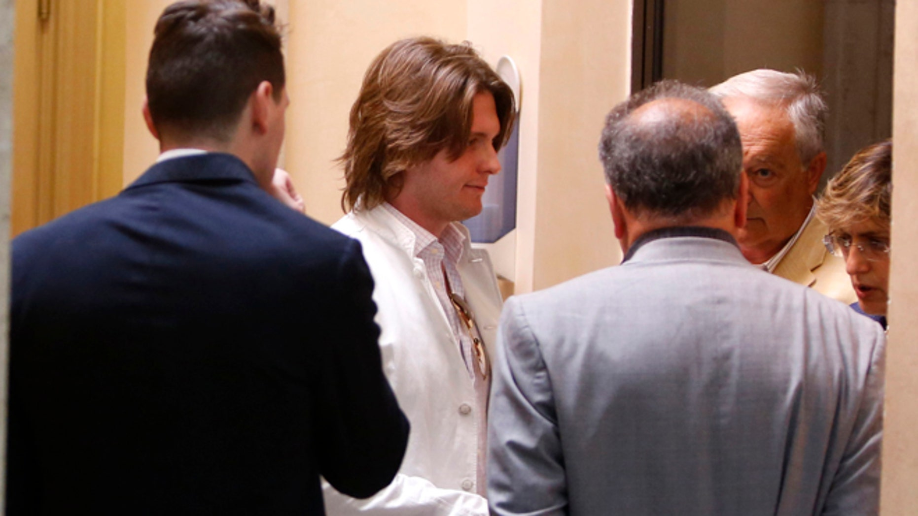 July 1, 2014: Raffaele Sollecito, second from left, and his father Francesco, second from right, listen to lawyers Luca Mauri, center with gray suit, and Giulia Bongiorno, right, before giving a press conference in Rome. (AP)