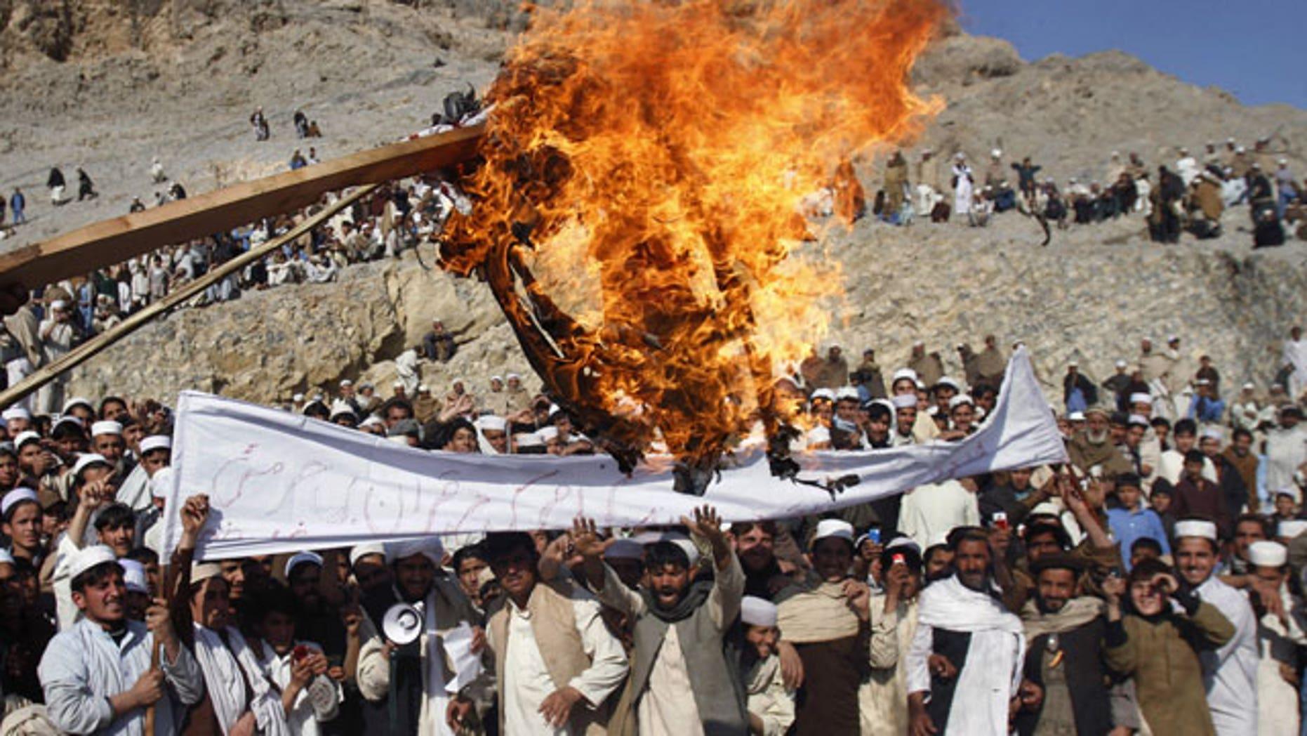 In this Feb. 24, 2012 file photo, Afghans burn an effigy representing U.S. President Barack Obama during an anti-U.S. protest in Ghani Khail, east of Kabul, Afghanistan.