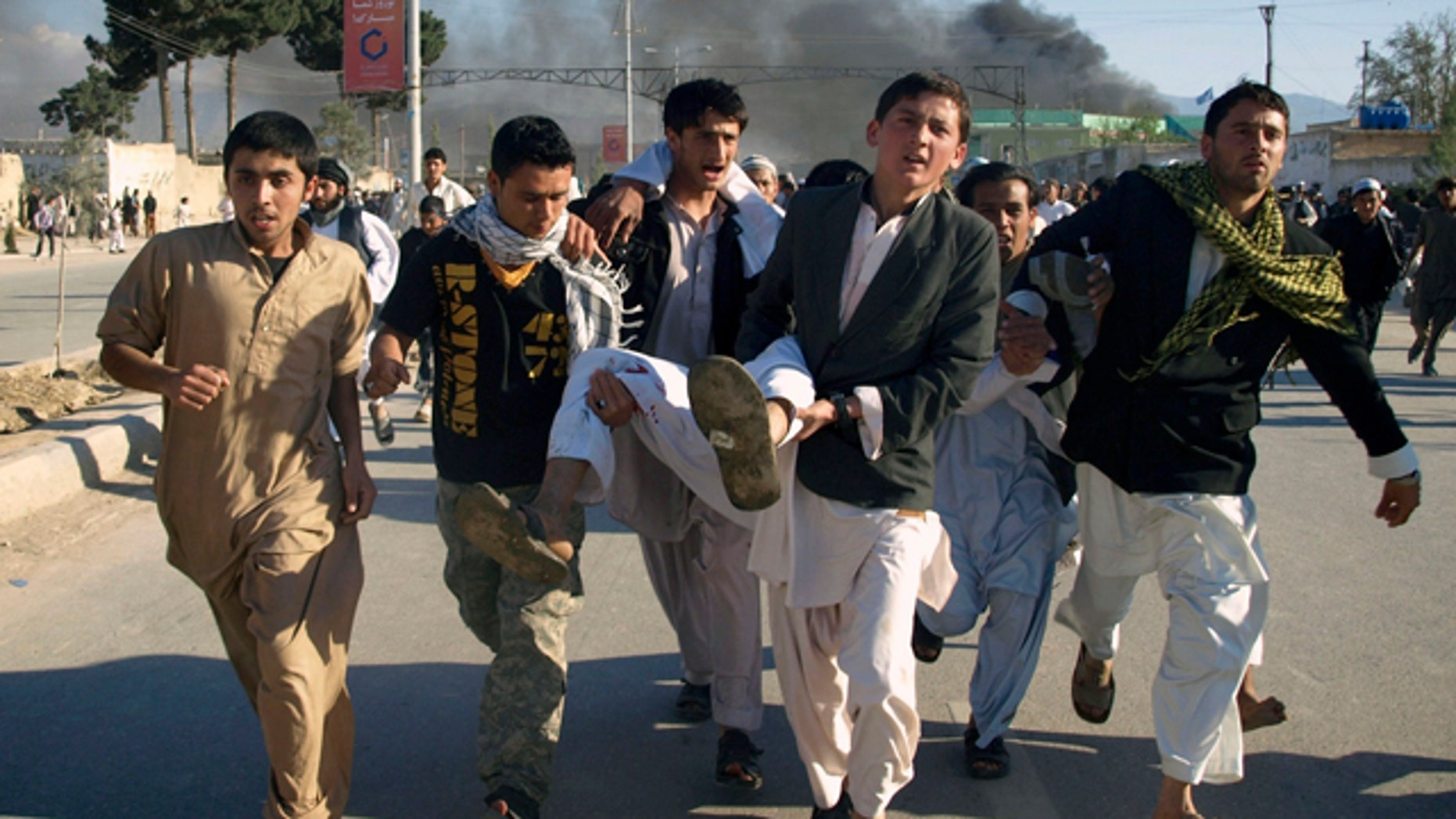 April 1: Afghans carry a man who was wounded following an attack on UN's office during a demonstration to condemn the burning of a copy of the Muslim holy book by a Florida pastor, in Mazar-i- Sharif north of Kabul, Afghanistan. An Afghan official says seven people have been killed at a U.N. office in the northern city of Mazar-i-Sharif when a Koran-burning protest turned violent. (AP)