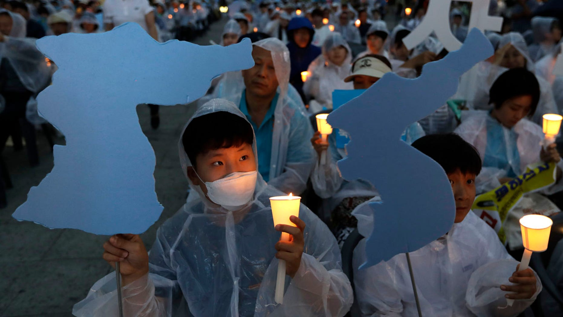 Participants hold candles and cardboards cutout of the map of Korean peninsula during a rally wishing for a successful summit between U.S. President Donald Trump and North Korea's leader Kim Jong Un and peace on the Korea peninsular near the U.S. embassy in Seoul, South Korea, Saturday, June 9, 2018. A planned summit between Trump and Kim will be held in Singapore on June 12.