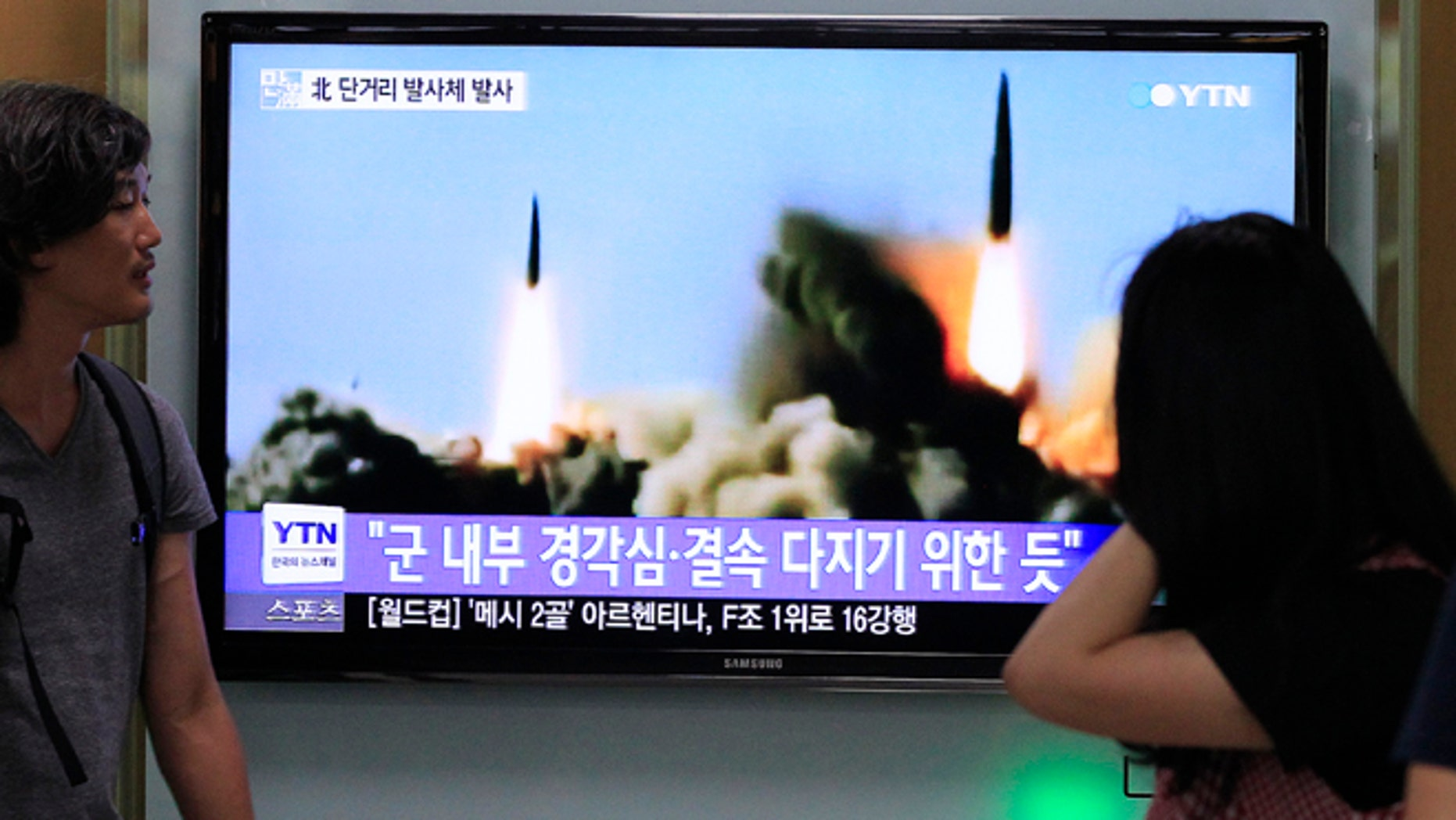June 26, 2014: People watch a TV news program showing the missile launch conducted by North Korea, at Seoul Railway Station in Seoul, South Korea.