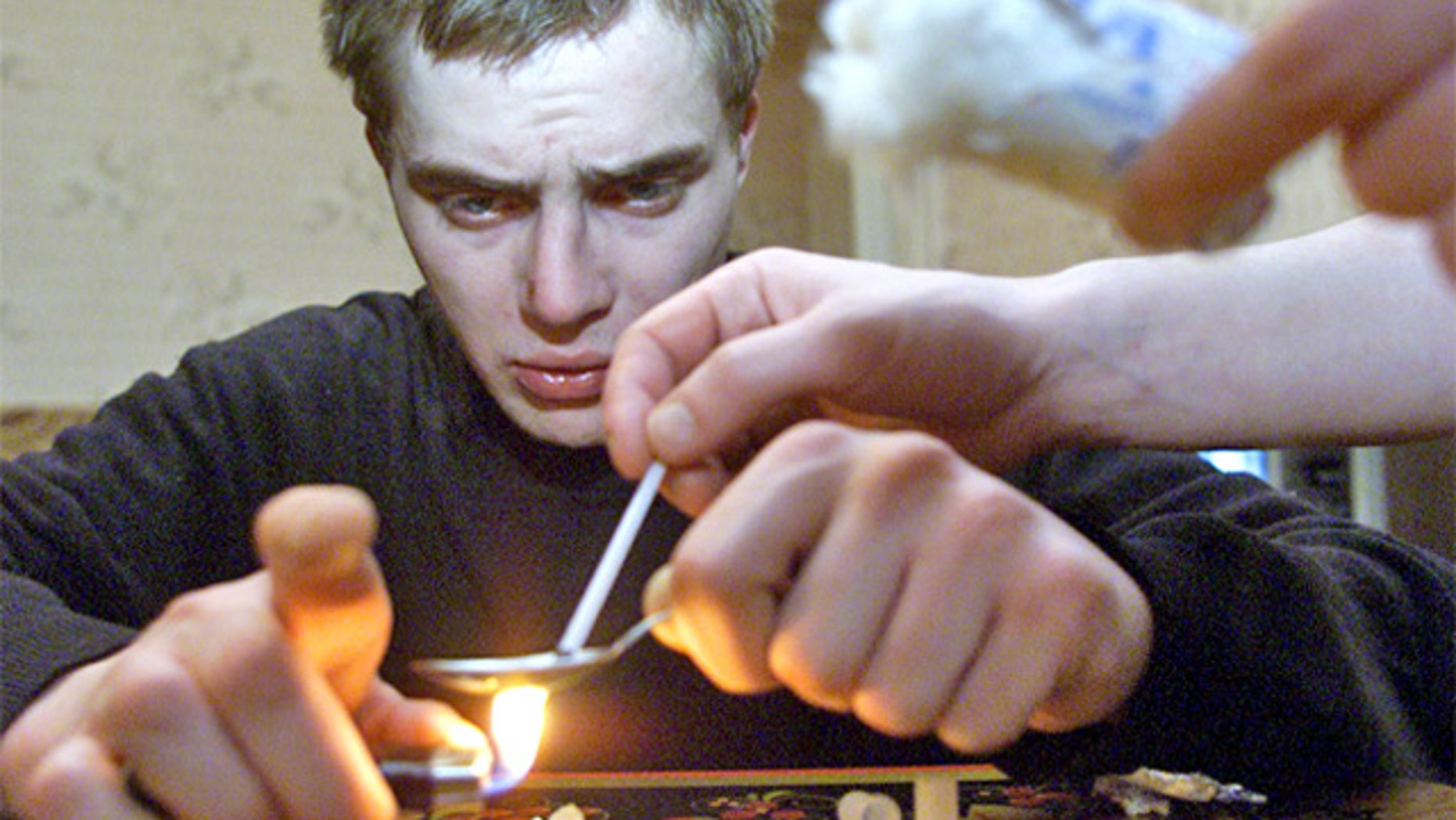 A man prepares heroin in Zhukovsky, Russia, near Moscow. To produce krokodil, which has a comparable effect to heroin but is much cheaper to make, users mix codeine with gasoline, paint thinner, iodine, hydrochloric acid and red phosphorous.