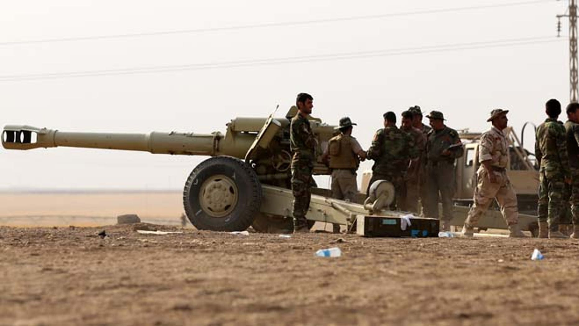 Oct. 1, 2014: Kurdish peshmerga forces stand by their armed vehicles in Mahmoudiyah, Iraq, a day after they take control of the village from the Islamic State group, as they patrol. Iraqi Kurdish fighters on the front lines of battle say they have yet to receive the heavy weapons and training pledged by the United States and nearly a dozen other countries to help them push back the Sunni militants.