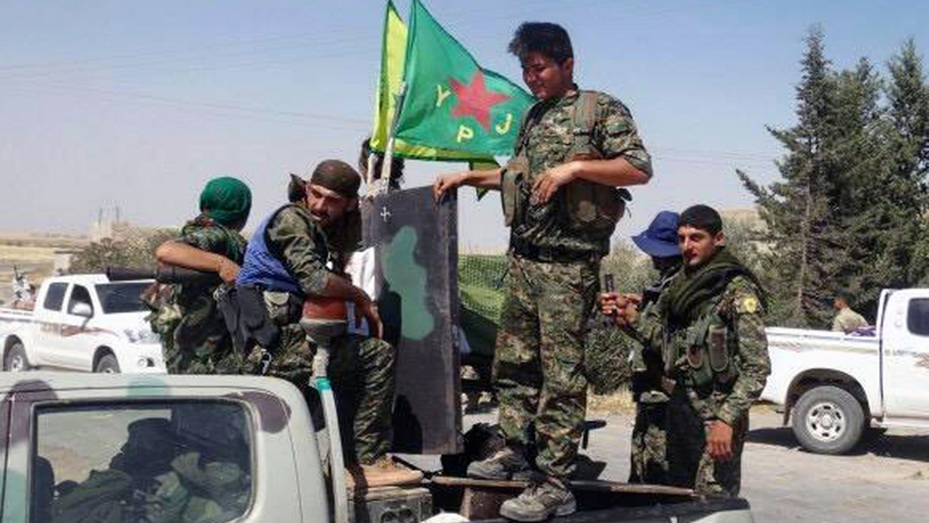 In this file photo released on Tuesday, June 23, 2015, provided by the Kurdish fighters of the People's Protection Units (YPG), which has been authenticated based on its contents and other AP reporting, Kurdish fighters of the YPG, sit on their pickup in the town of Ein Eissa, north of Raqqa city, Syria.