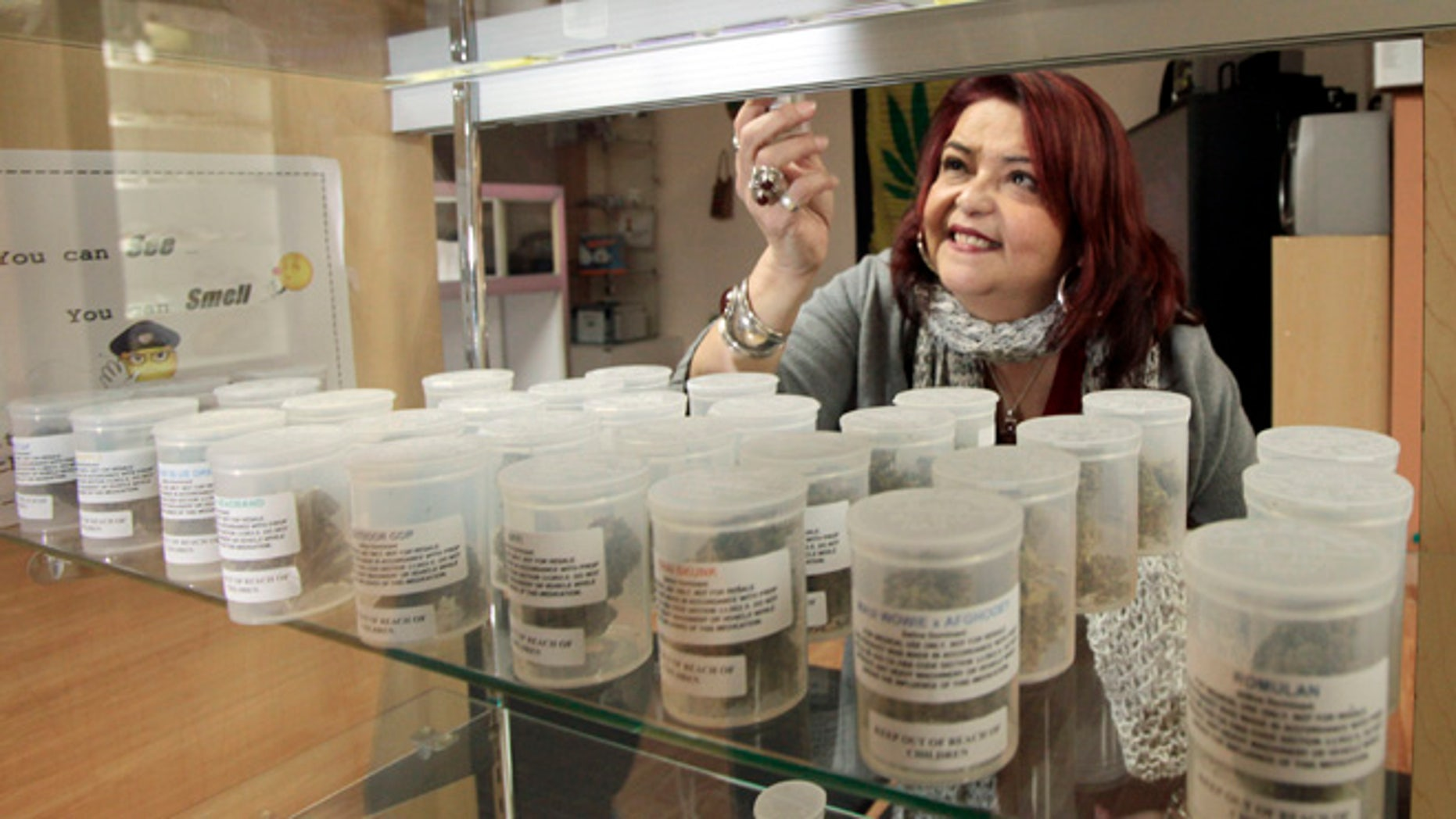 Jan. 26, 2010: A worker with Pure Life Alternative Wellness Center selects a vial of marijuana for a client at her store in Los Angeles.