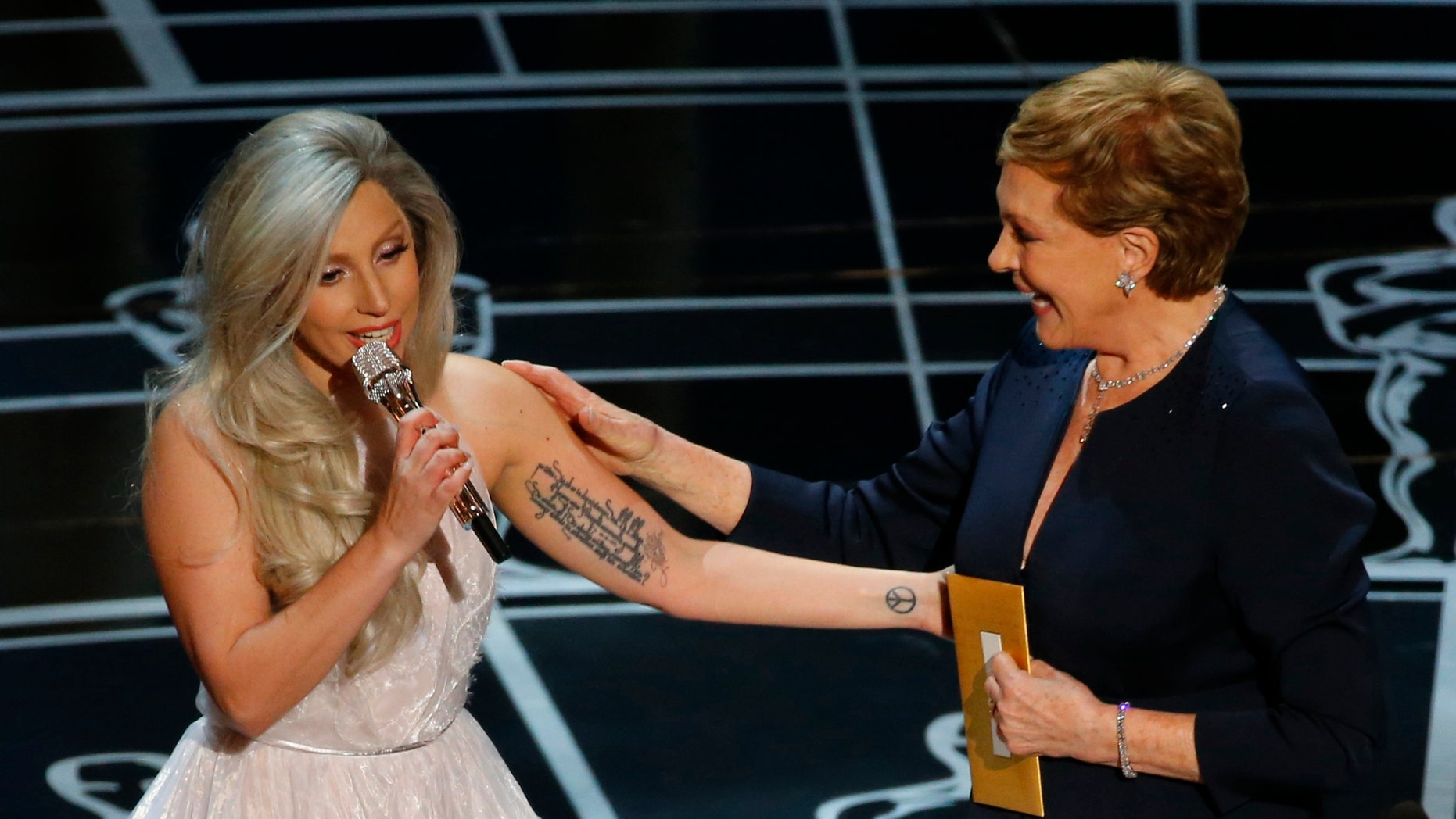 Singer Lady Gaga (L) pays tribute to Julie Andrews after performing songs from the Sound of Music at the 87th Academy Awards in Hollywood, California February 22, 2015.  REUTERS/Mike Blake (UNITED STATES TAGS:ENTERTAINMENT) (OSCARS-SHOW) - RTR4QP5C