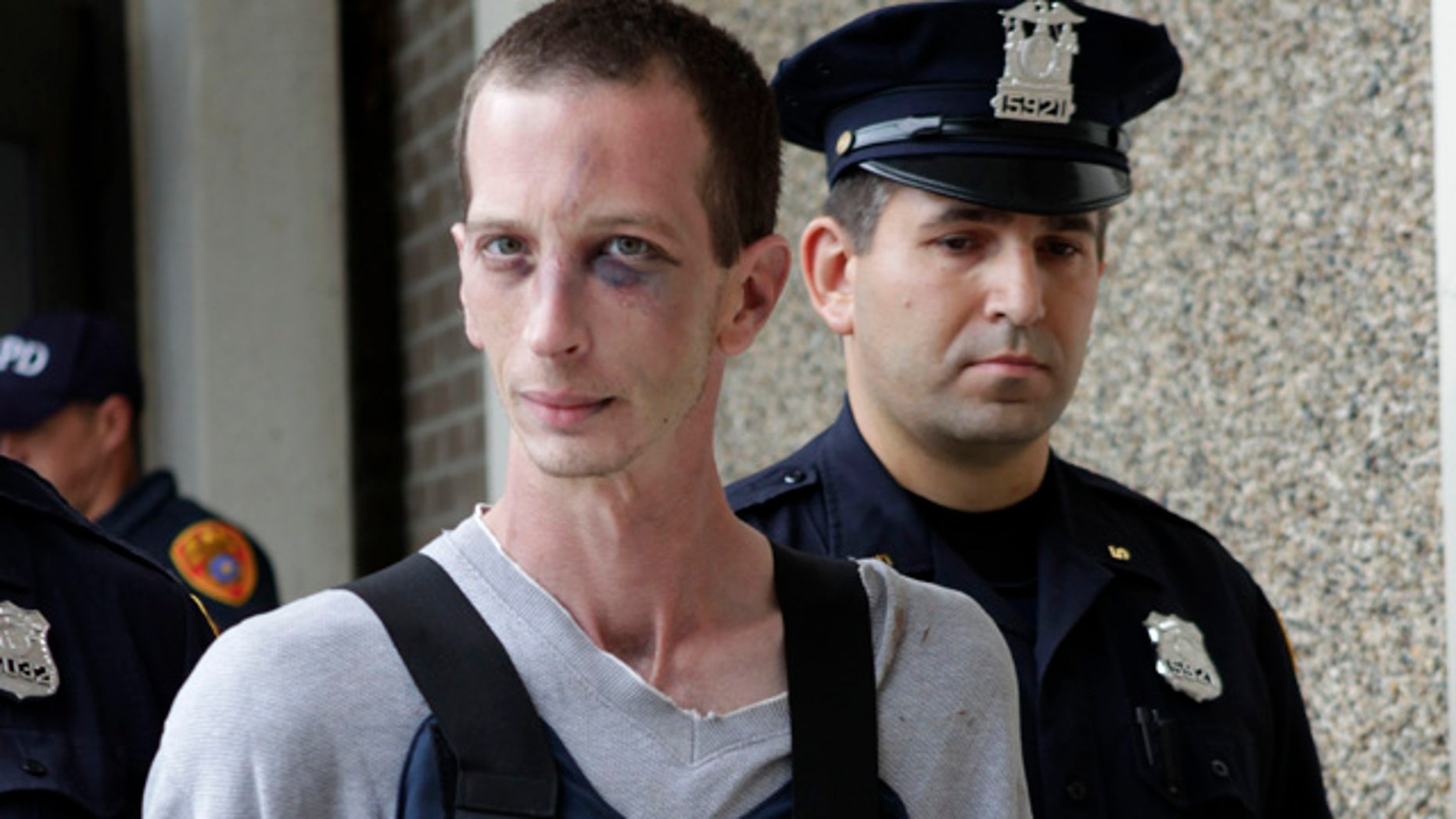 June 23: David Laffer is escorted out of a police station in Patchogue, N.Y.
