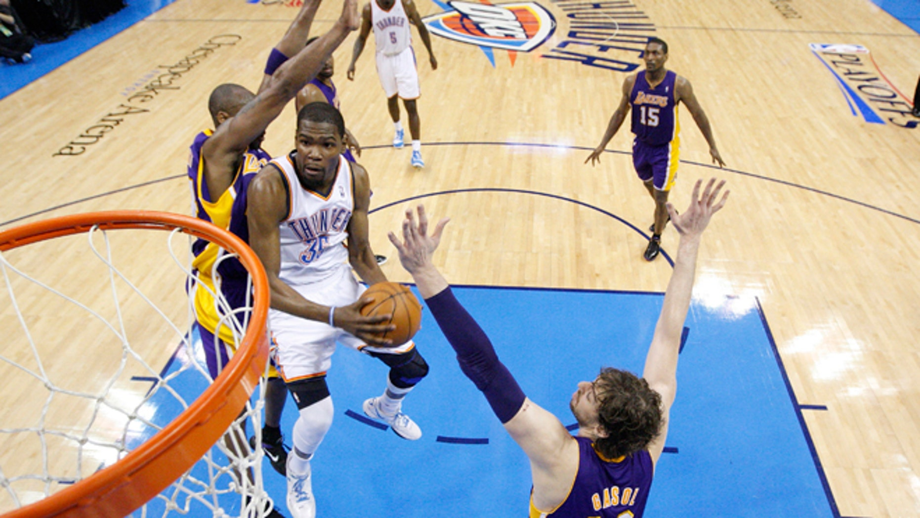 Oklahoma City Thunder forward Kevin Durant, center, goes up for a shot between Los Angeles Lakers guard Kobe Bryant, left and forward Pau Gasol (16) in the second quarter in Game 2 of an NBA basketball playoffs Western Conference semifinal, in Oklahoma City on Wednesday, May 16, 2012. Oklahoma City won 77-75. (AP Photo/Sue Ogrocki, Pool)