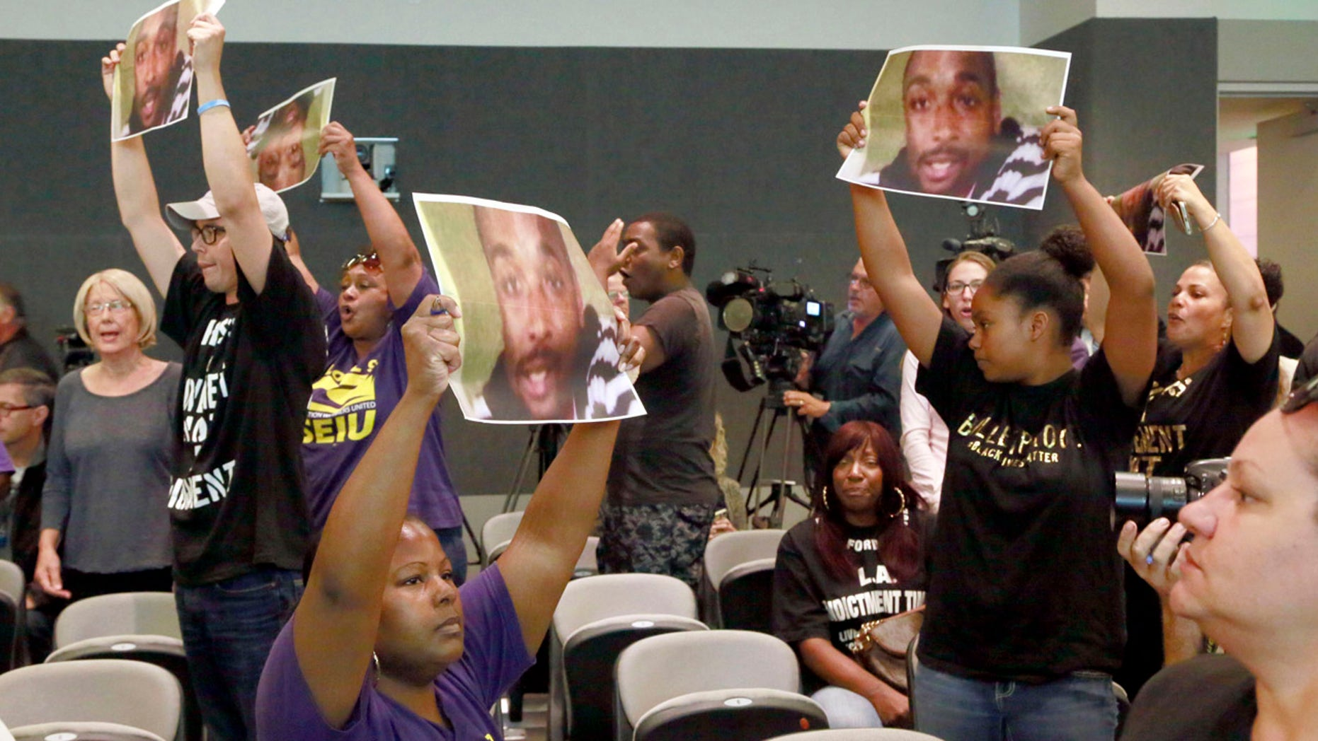 Aug. 11, 2015: Protesters holding photos of Ezell Ford, chant for Los Angeles Police Chief Charlie Beck's firing during a Los Angeles Police Commission meeting in downtown Los Angeles.