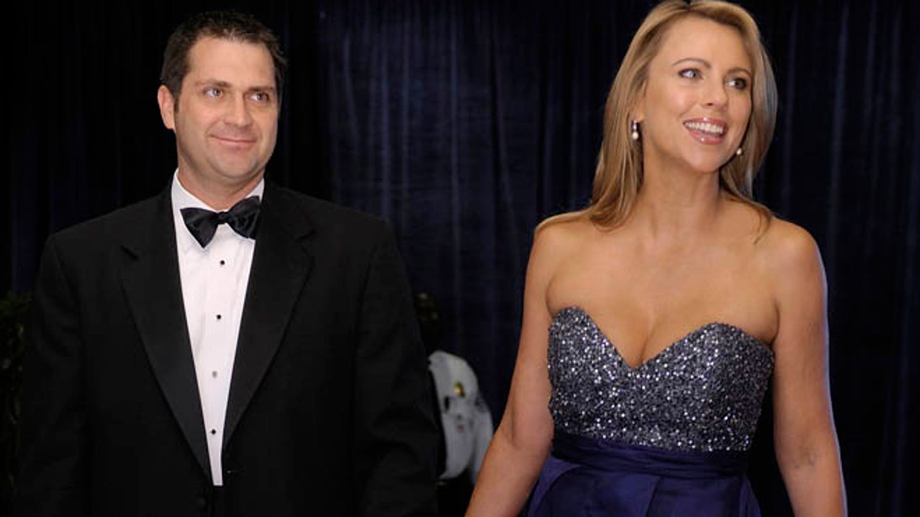 Lara Logan of CBS News and her husband Joseph Burkett stand on the red carpet as they arrive for the annual White House Correspondents' Association dinner in Washington, April 30, 2011. REUTERS/Jonathan Ernst    (UNITED STATES - Tags: POLITICS ENTERTAINMENT MEDIA) - RTR2LU14