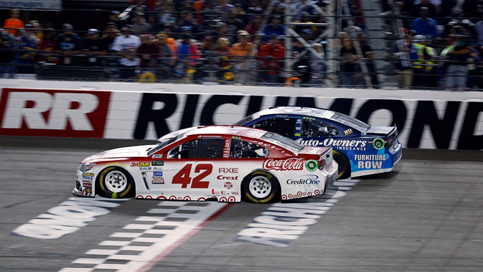 Kyle Larson (42) passes Martin Truex, Jr., (78) on the final restart to win the NASCAR Cup Series auto race at Richmond International Raceway in Richmond, Va., Saturday, Sept. 9, 2017. (AP Photo/Steve Helber)