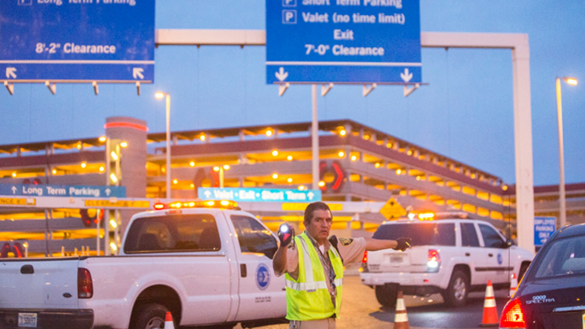 Officials redirect traffic after a shooting in a parking garage at McCarran International Airport on Monday, Sept. 19, 2016, in Las Vegas.