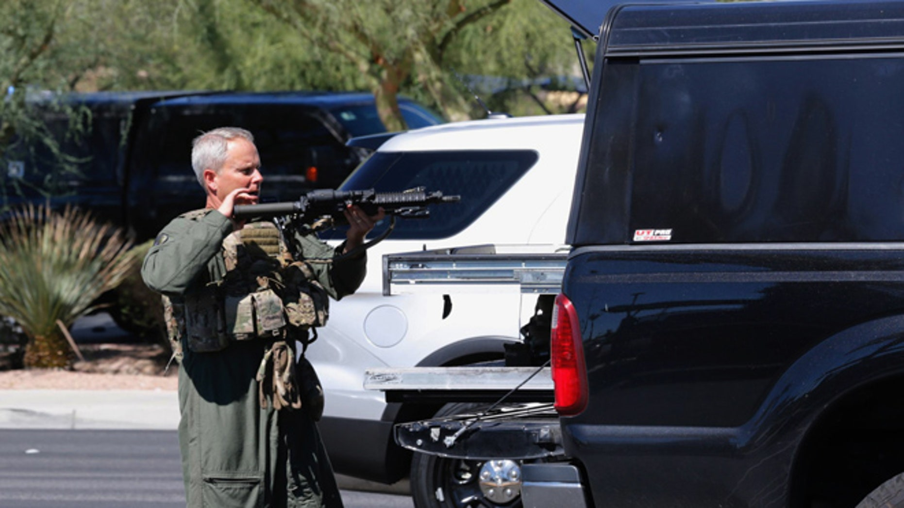 A member of the SWAT team holds a gun as officers investigate a shooting that occurred inside a coffee shop in Las Vegas on Sunday, Sept. 25, 2016. Police said two men got into an argument and then one pulled out a gun and opened fire. (Chitose Suzuki/Las Vegas Review-Journal via AP)