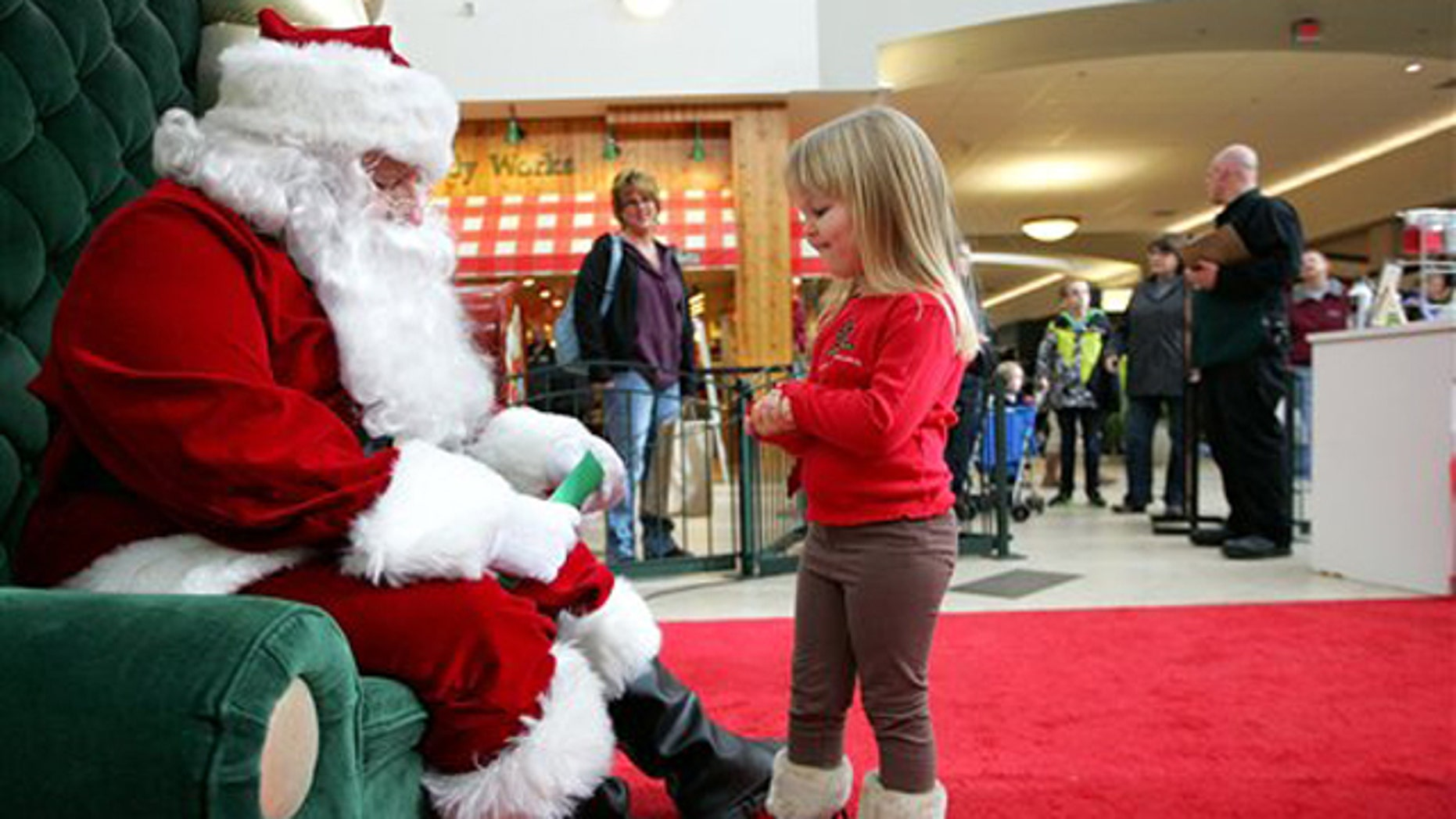 Dec. 23, 2010: Emma Schlichtmann, 3, of Potosi, Wis., tells Santa all the things she wants for Christmas while visiting him at a shopping mall in Dubuque, Iowa.