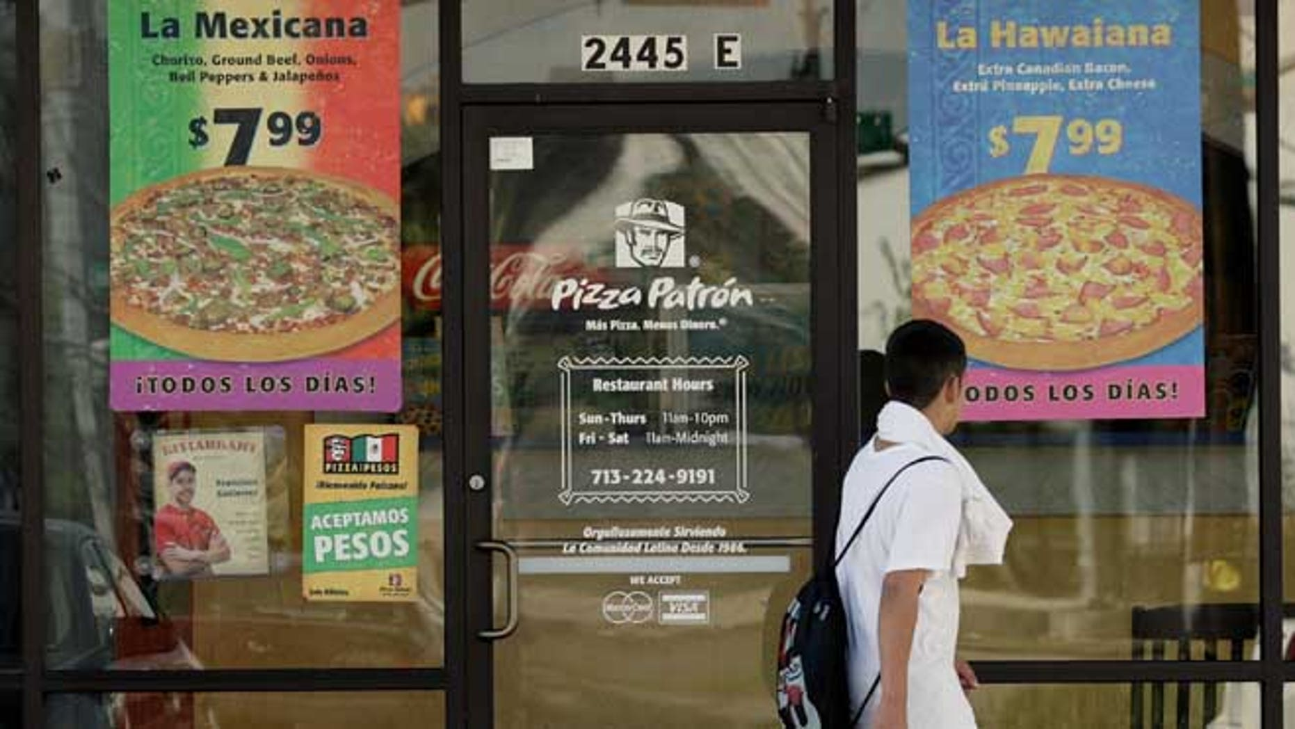 HOUSTON, TX - JANUARY 12:  A boy passes a Pizza Patron January 12, 2007, in Houston. The pizza chain now accepts Mexican pesos and U.S. dollars as payment. (Photo by Dave Einsel/Getty Images)