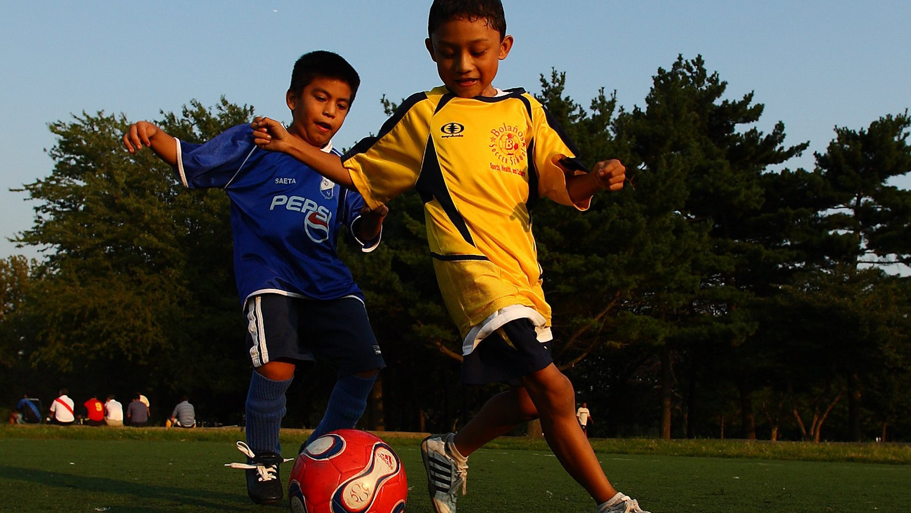 QUEENS, NY - SEPTEMBER 7:  Boys play a pickup game of soccer as their adult relatives participate in the Fedeiguayas Soccer League on September 7, 2007 at Flushing Meadows Park in the Queens Borough of  New York. A large Hispanic population from Mexico, Central and South America now living in New York congregate to this park every weekend to play soccer, and relax with family and friends. They play on ten soccer fields throughout the park and play goes from early morning till dusk.  The participants are highly skilled semi pro level players and each team dresses in the colors of their country and play as if it was their own  World Cup.  Matches are very competitive as the pride of each team's country is on the line.  (Photo by Al Bello/Getty Images)