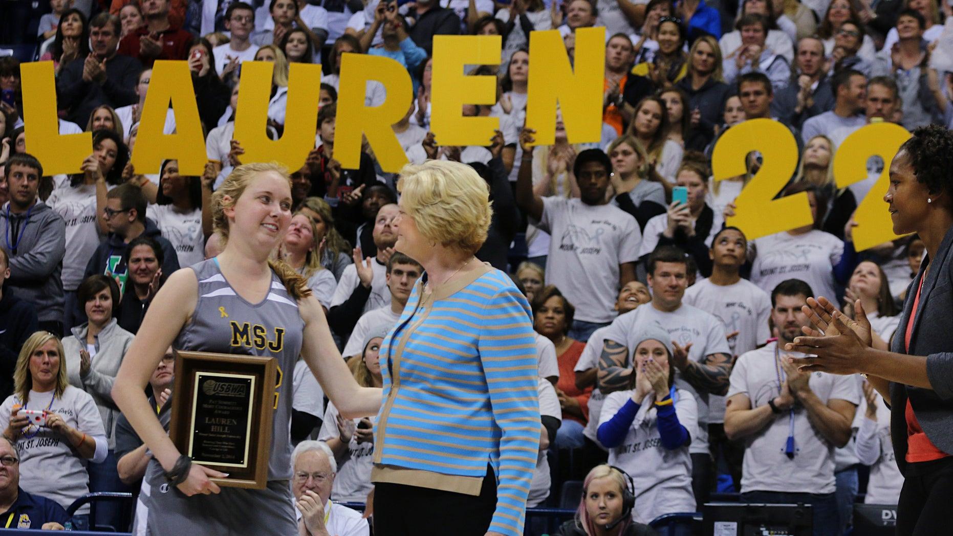Nov. 2, 2014: Mount St. Joseph's Lauren Hill hugs Pat Summit after receiving the Pat Summitt Award during halftime of her first NCAA college basketball game against Hiram University at Xavier University in Cincinnati on Sunday