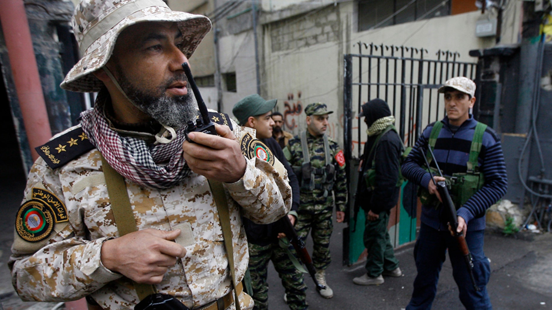 A Palestinian officer from the Fatah movement, speaks on a walkie talkie as others hold their weapons in the Ein el-Hilweh refugee camp, in the southern port city of Sidon, Lebanon, Wednesday, March. 1, 2017. The U.N. says it is suspending services in the conflict-torn Ein el-Hilweh Palestinian camp in south Lebanon for the third straight day. At least eight civilians, including a thirteen year old boy and a UN staffer, have been wounded in the latest round of violence to consume the camp, according to a statement released jointly by the U.N.'s child relief and Palestinian relief agencies, on Tuesday. (AP Photo/Mohammed Zaatari)