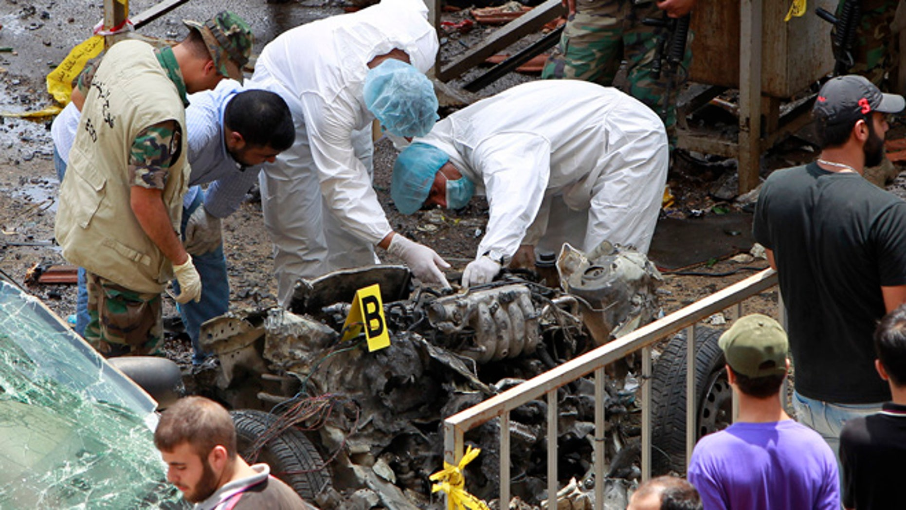 July 9, 2013: Forensic experts inspect the remnants of a car bomb at the scene of a bombing in the Beir el-Abed, a southern suburb of Beirut, Lebanon. A large explosion rocked a stronghold of the Shiite militant Hezbollah group south of the Lebanese capital Tuesday, setting several cars on fire, sending a thick plume of black smoke billowing into the sky and wounding more than a dozen people, security officials said.