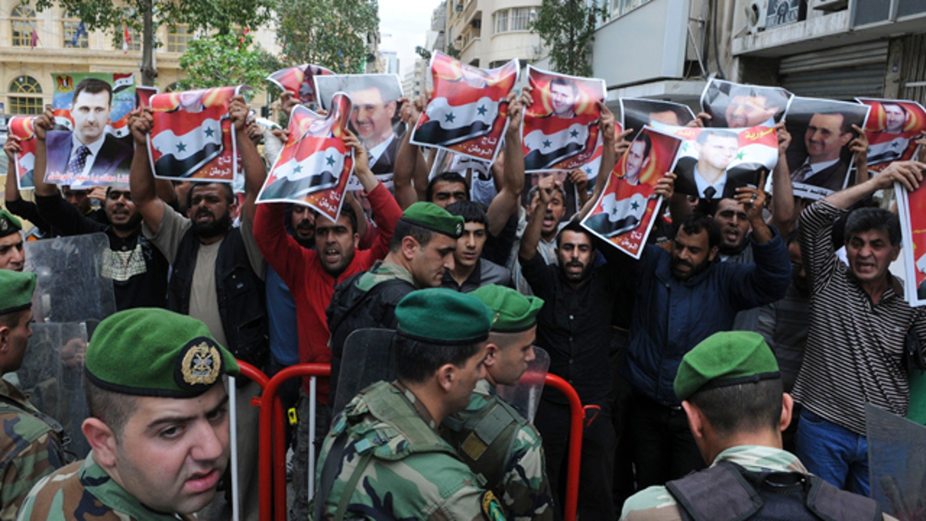 """April 29: Lebanese soldiers stand guard as Syrian protesters carry pictures of Syrian President Bashar Assad and shout pro-government slogans in front of the Syrian embassy in Beirut, Lebanon. The banned Muslim Brotherhood urged Syrians to take to the streets on Friday as activists called for a """"Day of Rage"""" against Assad's regime, which has stepped up its deadly crackdown on protesters by unleashing the army along with snipers and tanks. The Arabic on Assad's picture reads:"""" The crown of the nation."""" (AP)"""