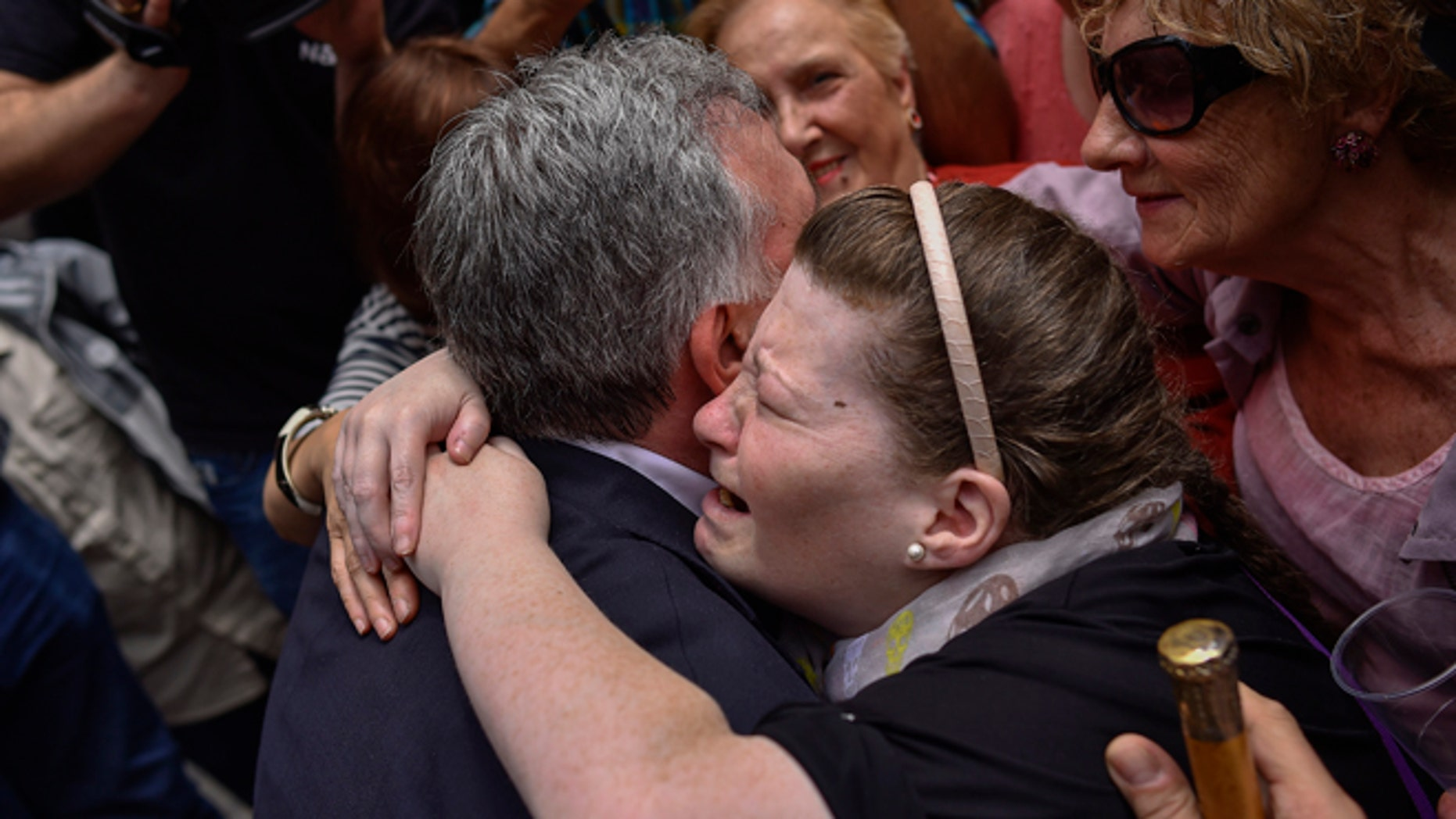 June 13, 2015: A woman cries as she embraces Pamplona's new Mayor and member of the Basque independence party EH Bildu, Joseba Asiron, left, in Ayuntamiento Square, in Pamplona, northern Spain. (AP)