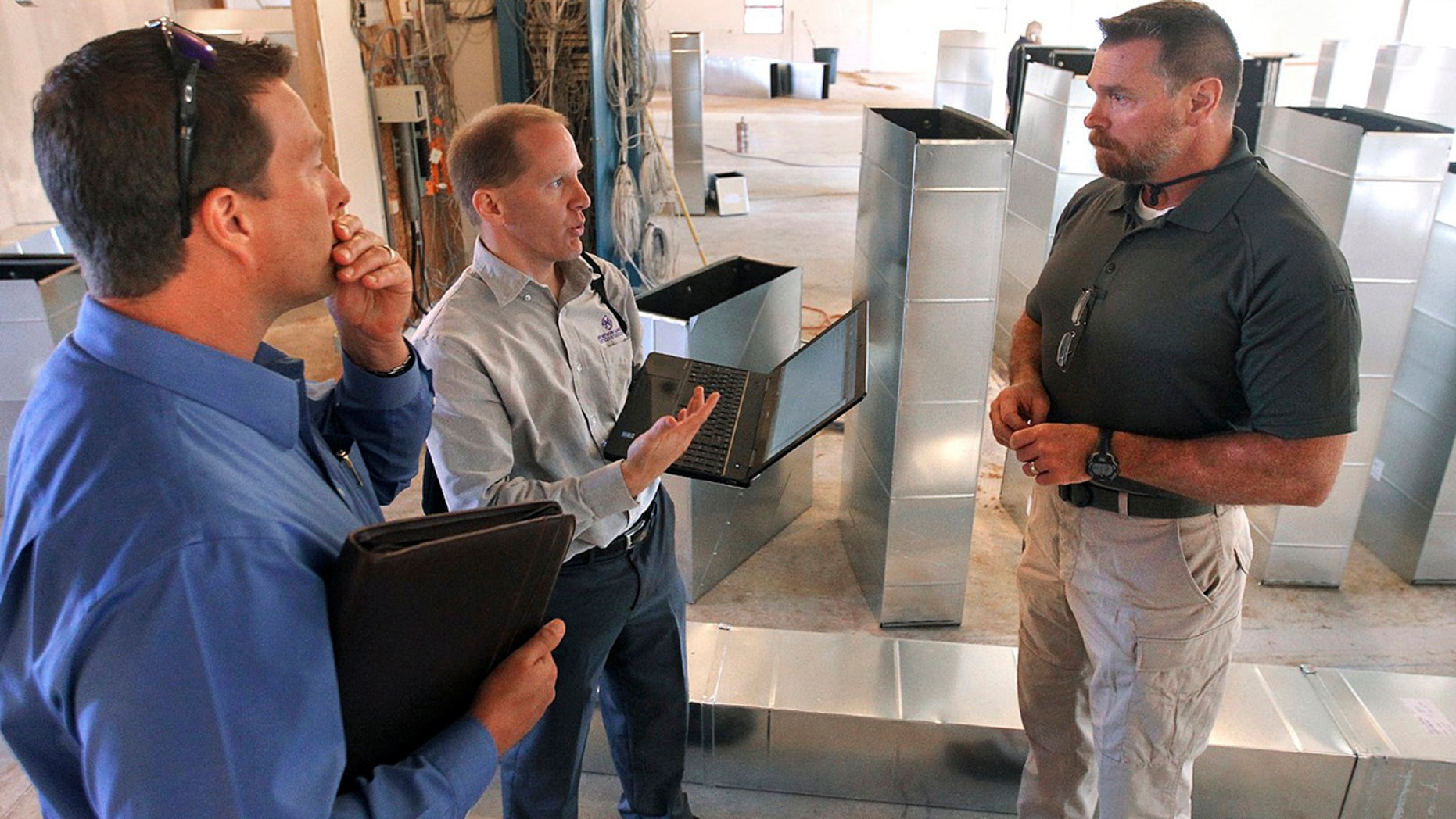 In this Sept. 29, 2015, photo, Scott Abbott, a retired Illinois State Police colonel, speaks with Mark Lewis, left, and Jeff Greer at the new medical marijuana dispensary being built in Collinsville, Ill. Abbott is the director of security and compliance with Health Central, Lewis is the director of finance and human resources for Health Central and Greer is with LRS Network Support. (Steve Nagy/Belleville News-Democrat via AP)