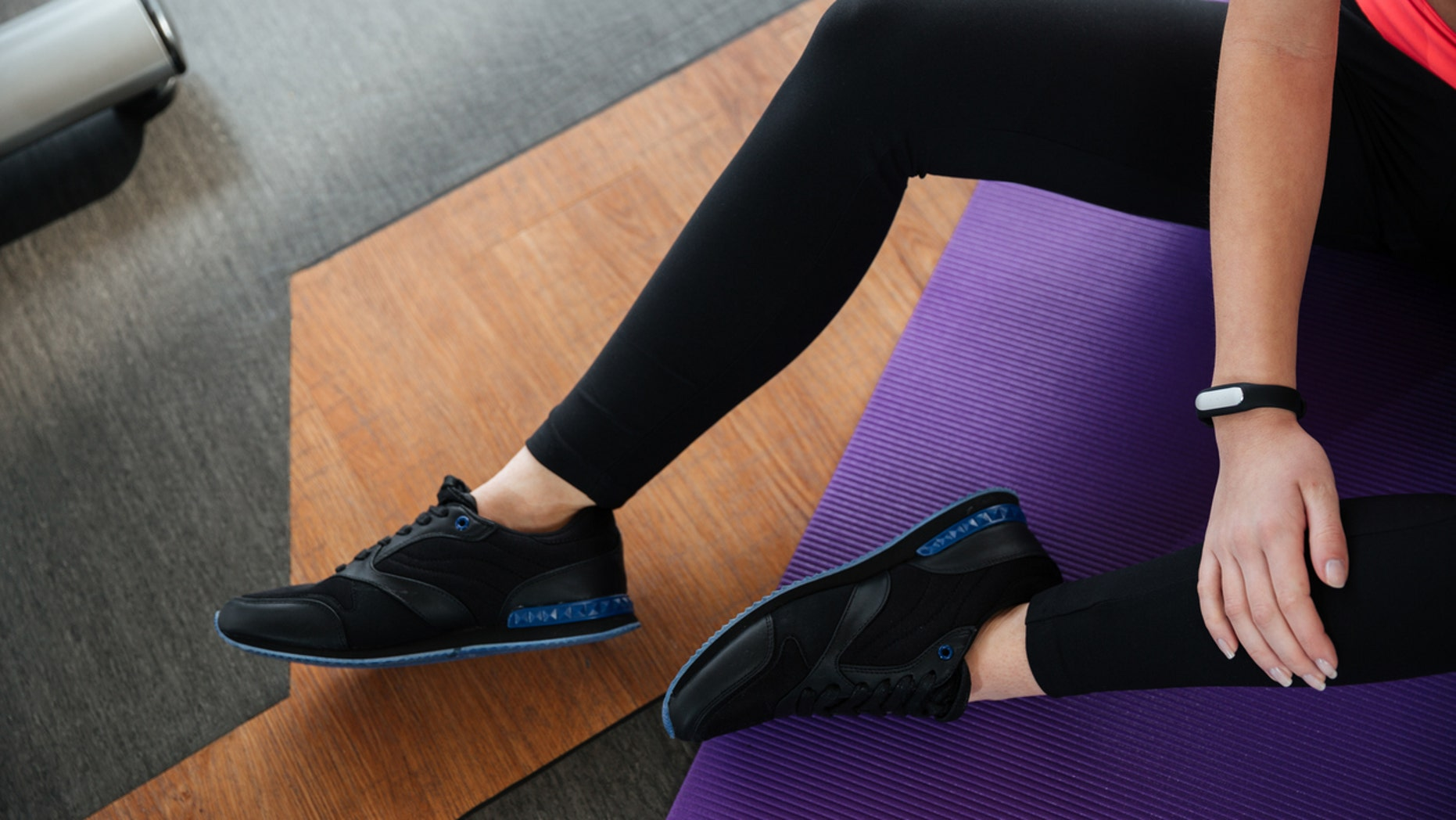 Top view of legs of young sportswoman with fitness tracker on hand in black leggings sitting on the floor in gym