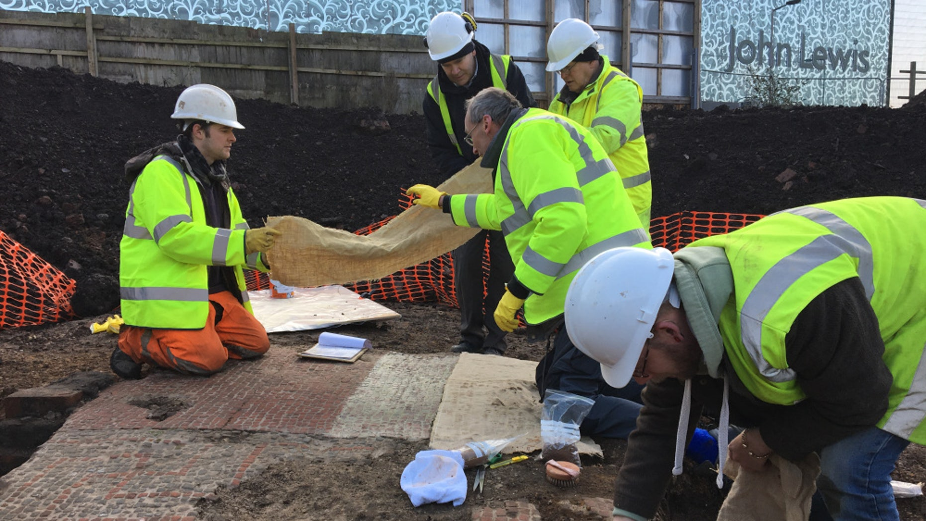 The team of conservators and archaeologists carefully prepare to lift the mosaic. (ULAS)