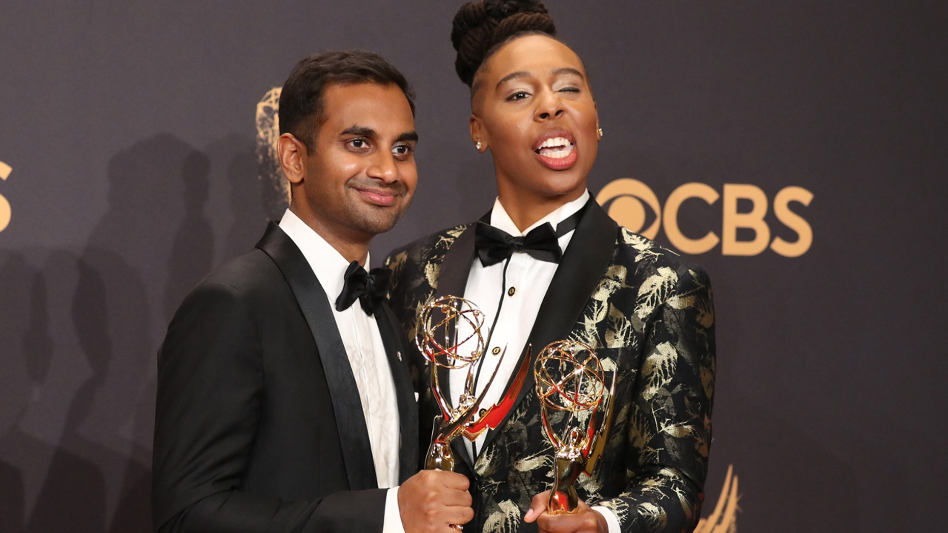 "Aziz Ansari (L) and Lena Waithe pose with the Emmy for Outstanding Writing for a Comedy Series for ""Master of None."""