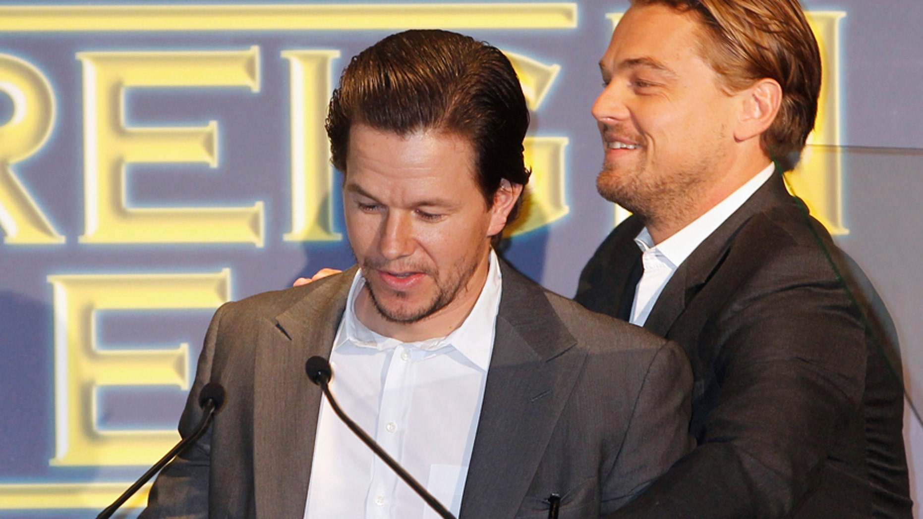 Actors Mark Wahlberg (L) and Leonardo DiCaprio are seen at the podium during the Hollywood Foreign Press Association's (HFPA) Annual Installation Luncheon in Beverly Hills, California August 4, 2011.