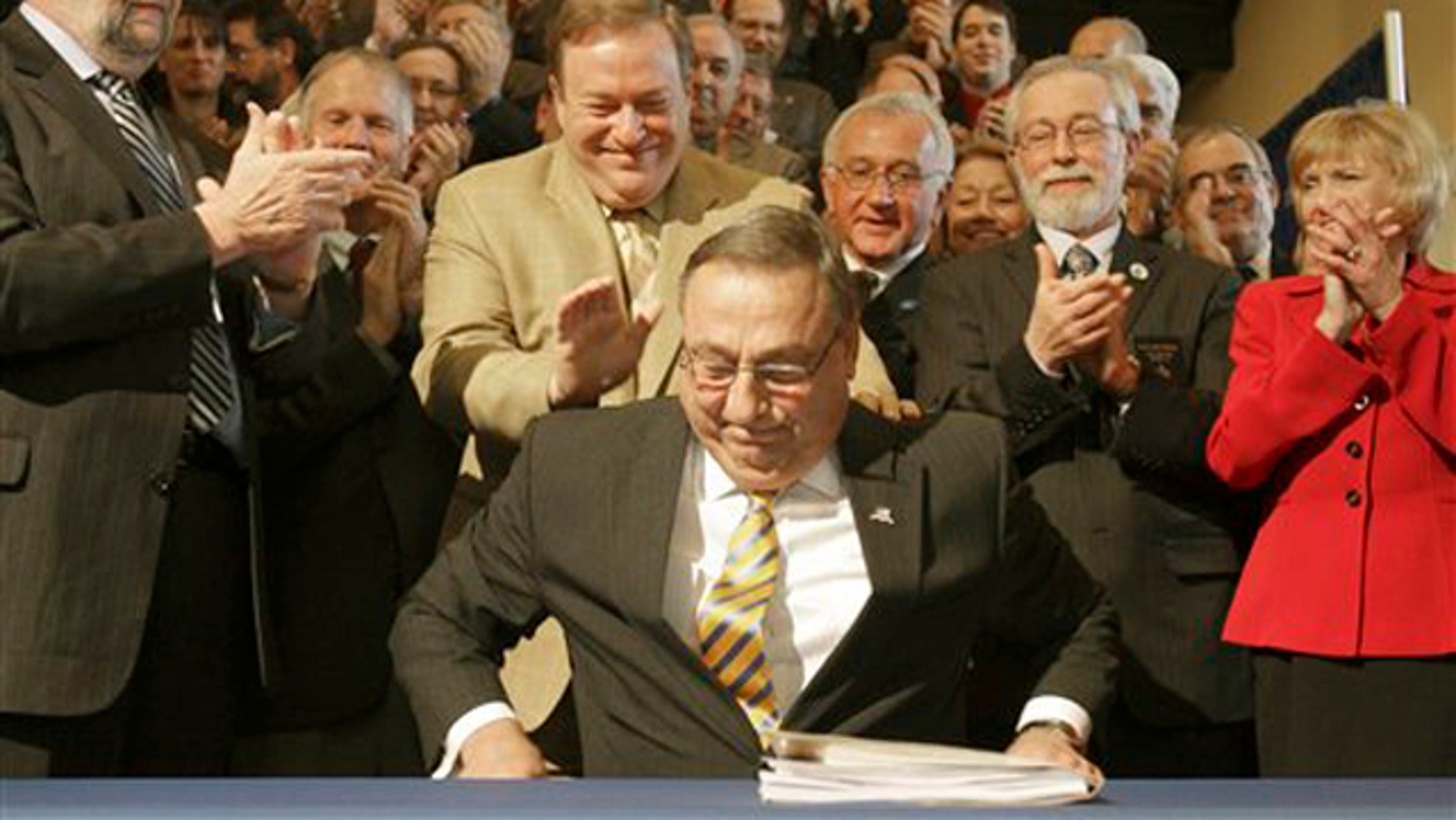 Maine Gov. Paul LePage smiles as he is congratulated after signing the health insurance overhaul bill at a State House signing ceremony in Augusta, Maine on May 17.