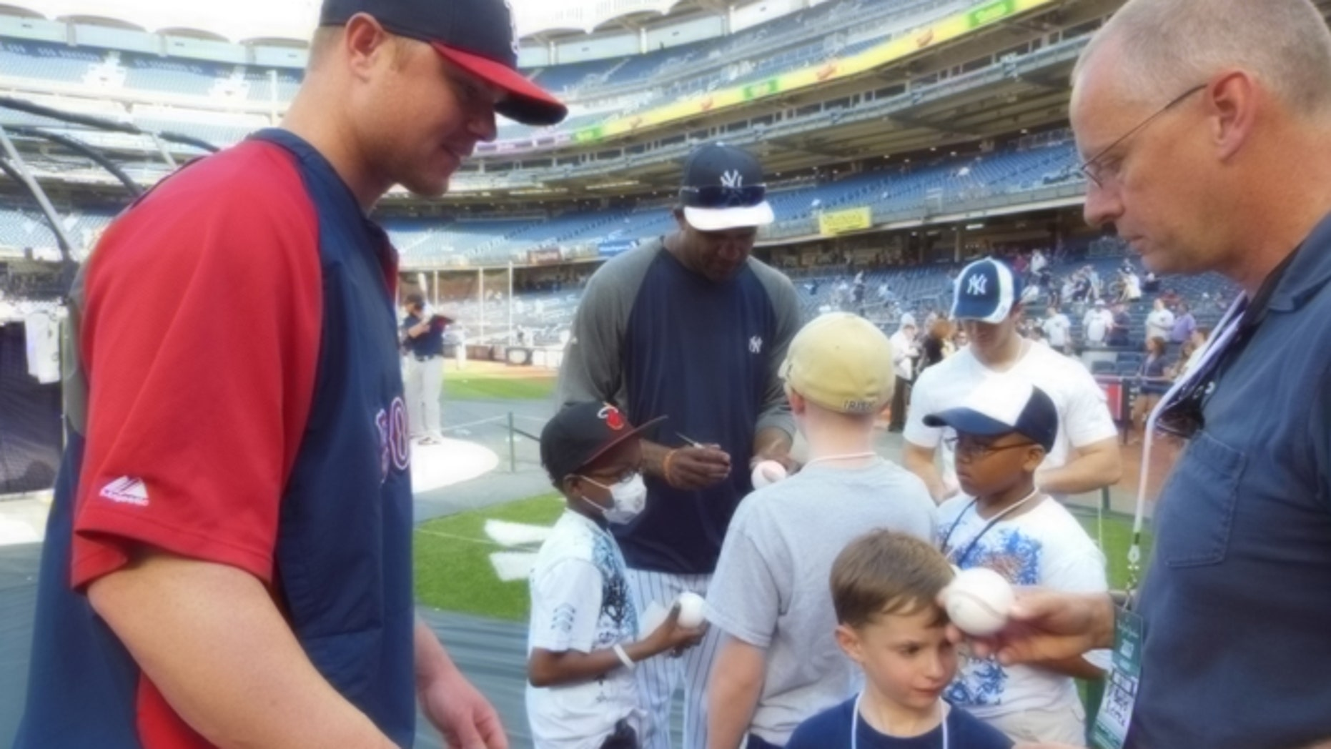 Red Sox ace Jon Lester makes time to sign autographs for kids with cancer, as does rival Yankees pitcher CC Sabathia (background).