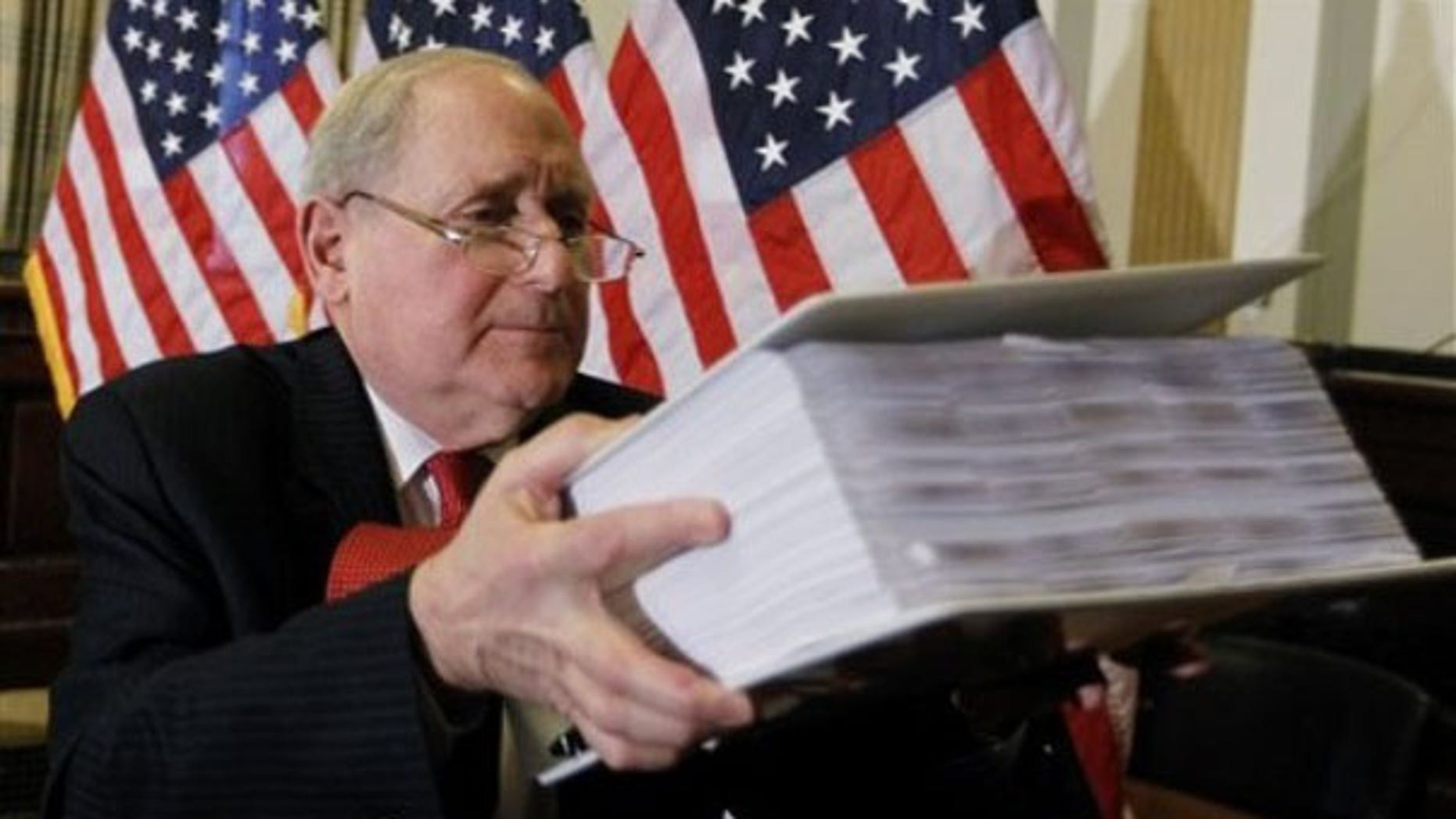 Sen. Carl Levin lifts documents on the role of investment banks in the Wall Street financial crisis as he briefs reporters on Capitol Hill April 26 ahead of the Goldman Sachs hearings. (AP Photo)