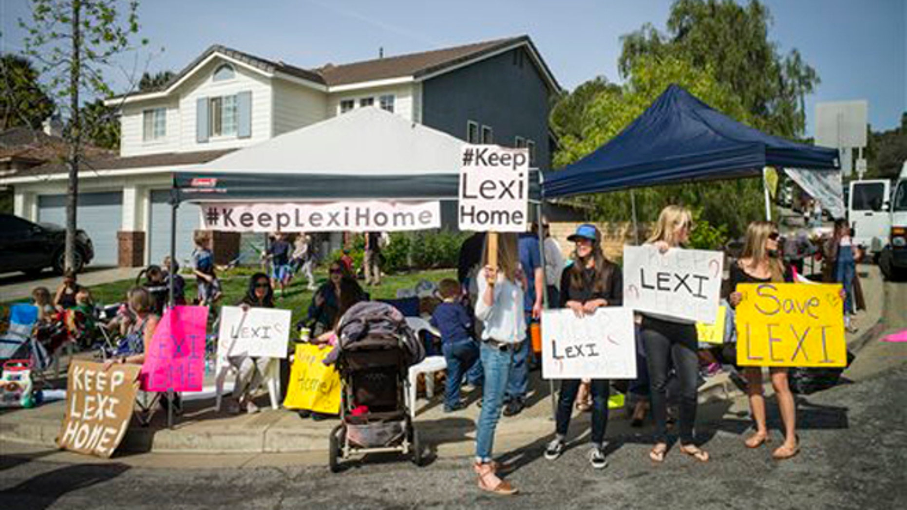 Supporters of Lexi's foster family hold a rally for the family outside Lexi's foster home in Santa Clarita, Calif., Monday, March 21, 2016.