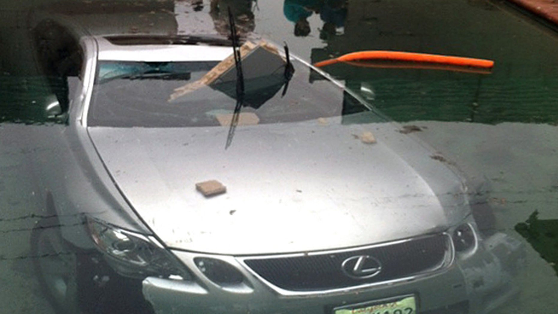 May 13, 2012: In this photo provided by Beatriz Diaz, officials investigate the scene where a man crashed his car through a wall and into a swimming pool in La Puente, Calif., early Sunday morning.
