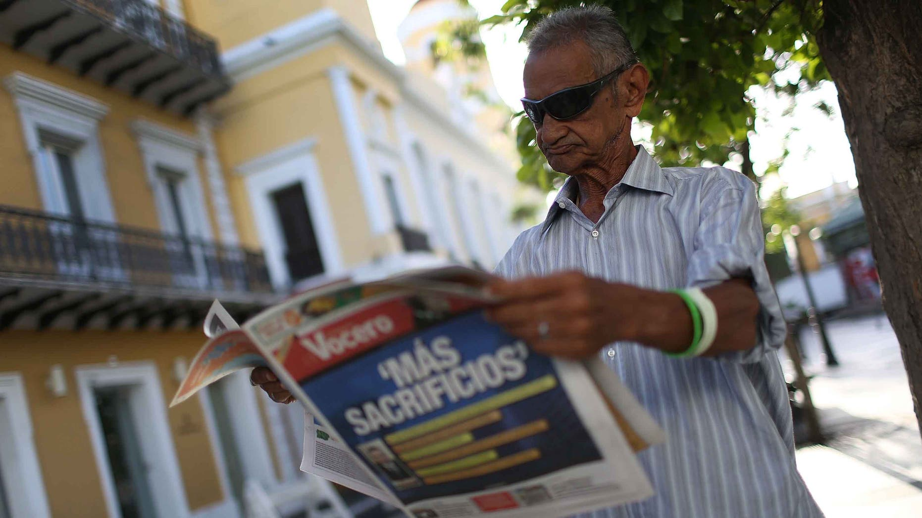 Jose Vasquez reads a newspaper with a Spanish headline that reads 'More sacrifices' in San Juan, Puerto Rico.