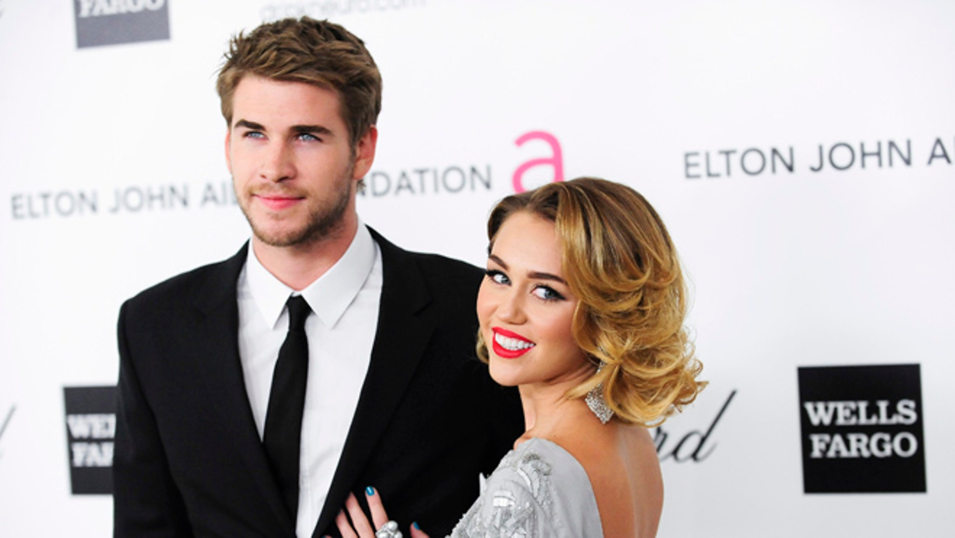 Liam Hemsworth and Miley Cyrus wore ugly Christmas sweaters to a party.