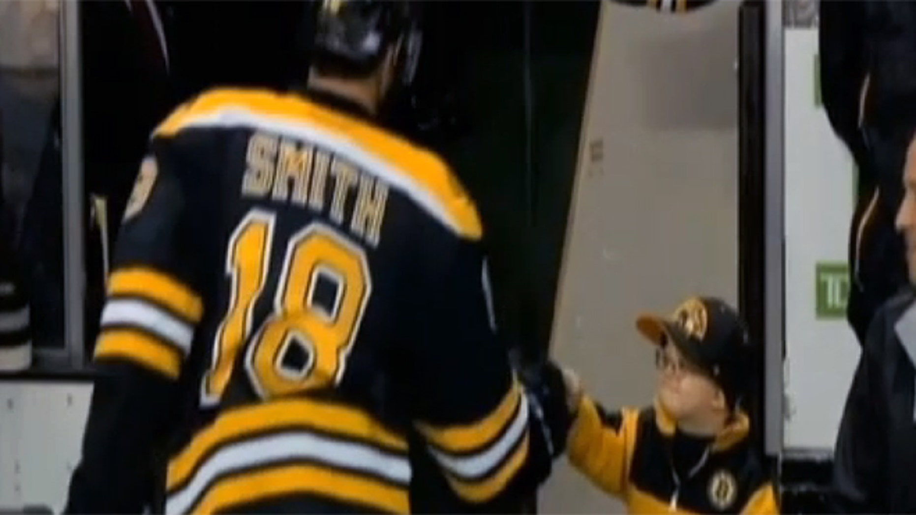 Eight-year-old Liam Fitzgerald shares a fist-bump with Reilly Smith of the Boston Bruins.