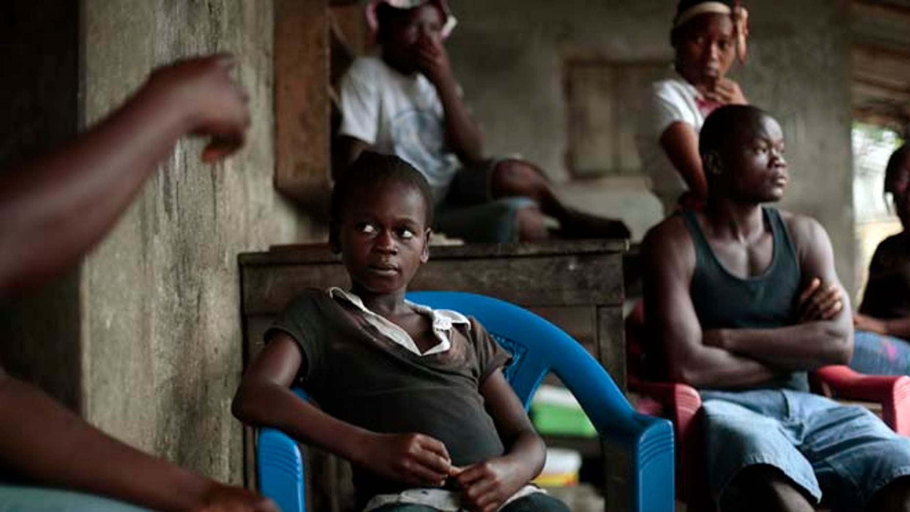 """Sept. 28, 2014: Kumba """"survivor"""" Fayiah, 11, sits with relatives in her  St Paul Bridge home in  Monrovia, Liberia. Fayah, who lost both parents and her sister, recovered from the Ebola virus and is now living with her extended family."""
