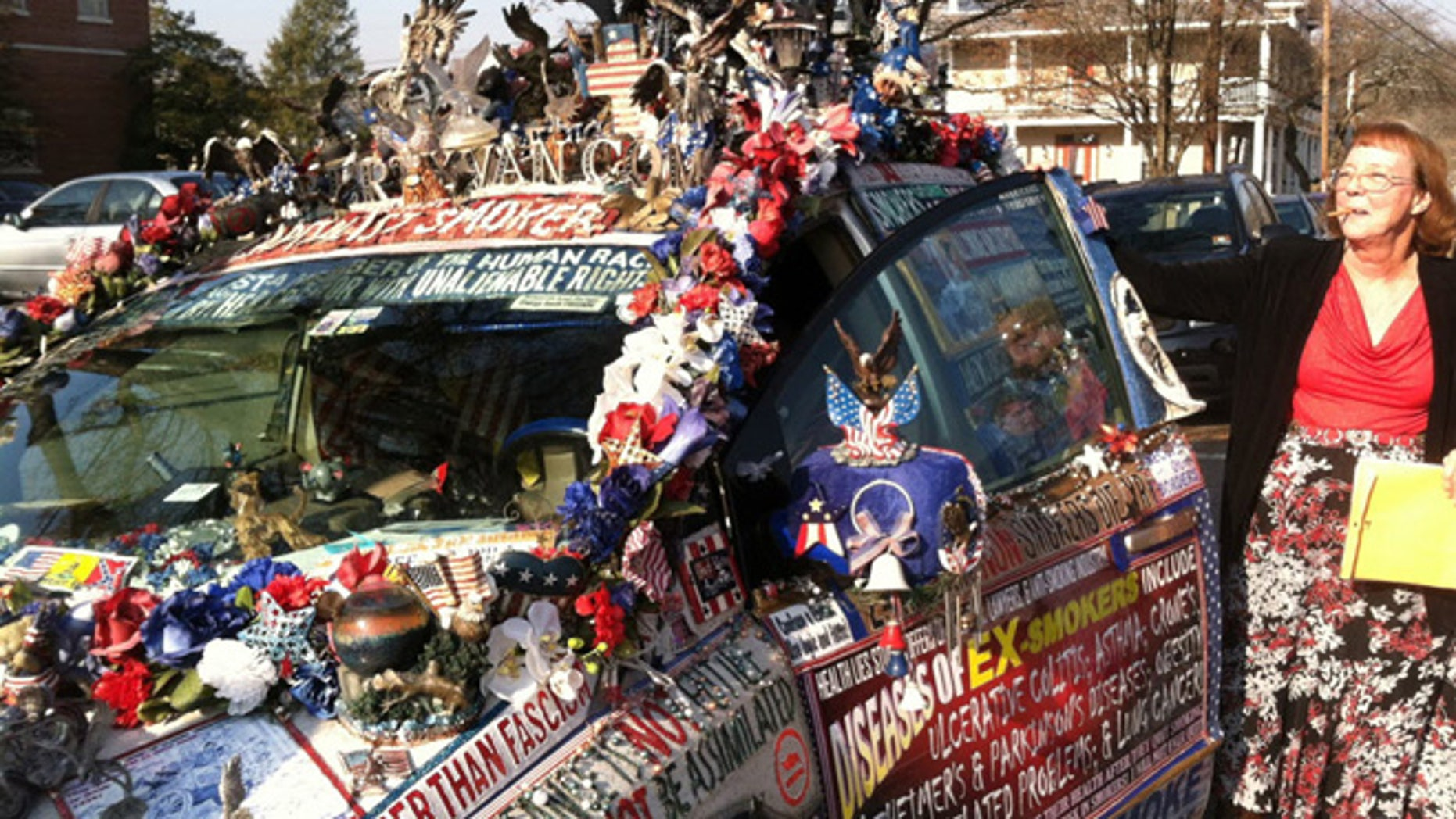 """Dec. 2, 2013: Smoking and guns advocate Lynda Farley stands outside her minivan, dubbed the """"Liberty Van"""" in Belvidere, N.J. Farley, 62, of Edmonton, Ky., fought a $56 ticket issued in September 2012 by New Jersey State Police for having an obstructed view."""