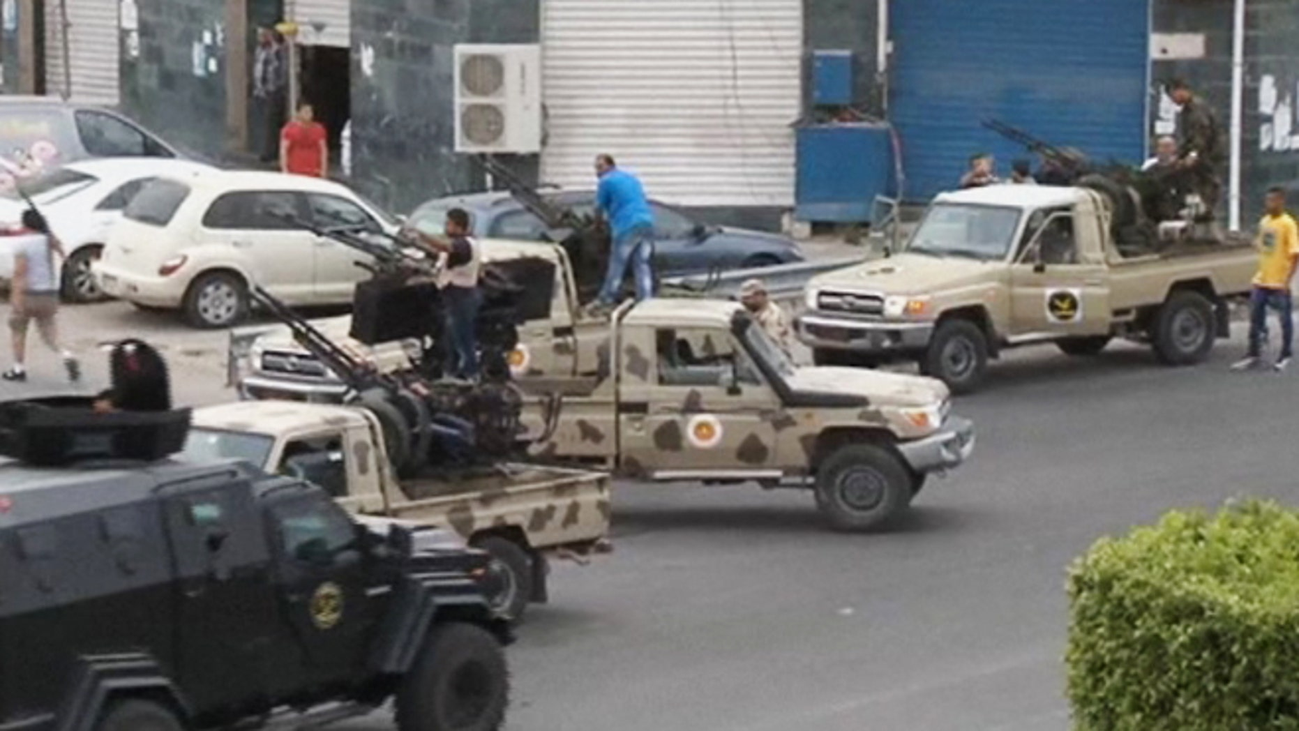 May 18, 2014: In this image made from video provided by the Libyan national army via AP Television, Tripoli joint security forces on vehicles with heavy artillery stand guard on the entrance road to the parliament area after troops of Gen. Khalifa Hifter targeted Islamist lawmakers and officials at the parliament in Tripoli, Libya.