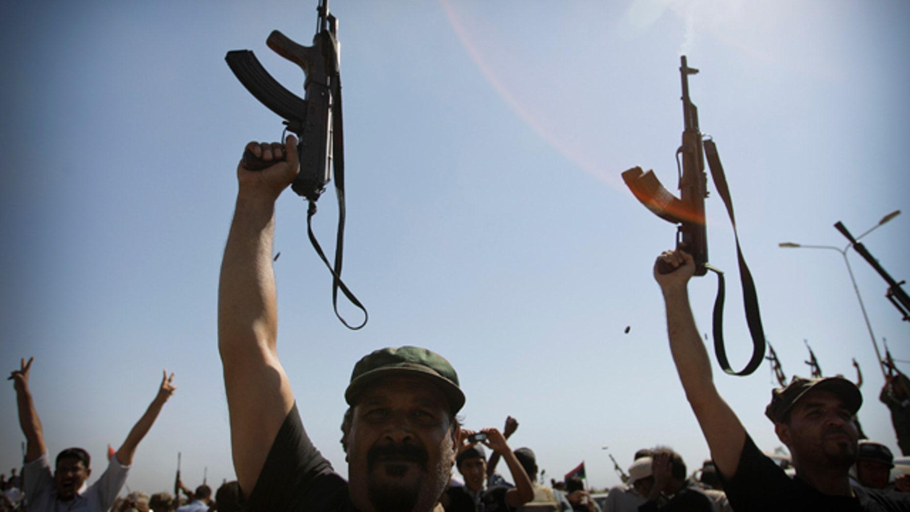 July 29: Libyan men shoot in the air during the funeral of Libyan rebels' slain military chief Abdel-Fattah Younis in the rebel-held town of Benghazi, Libya.