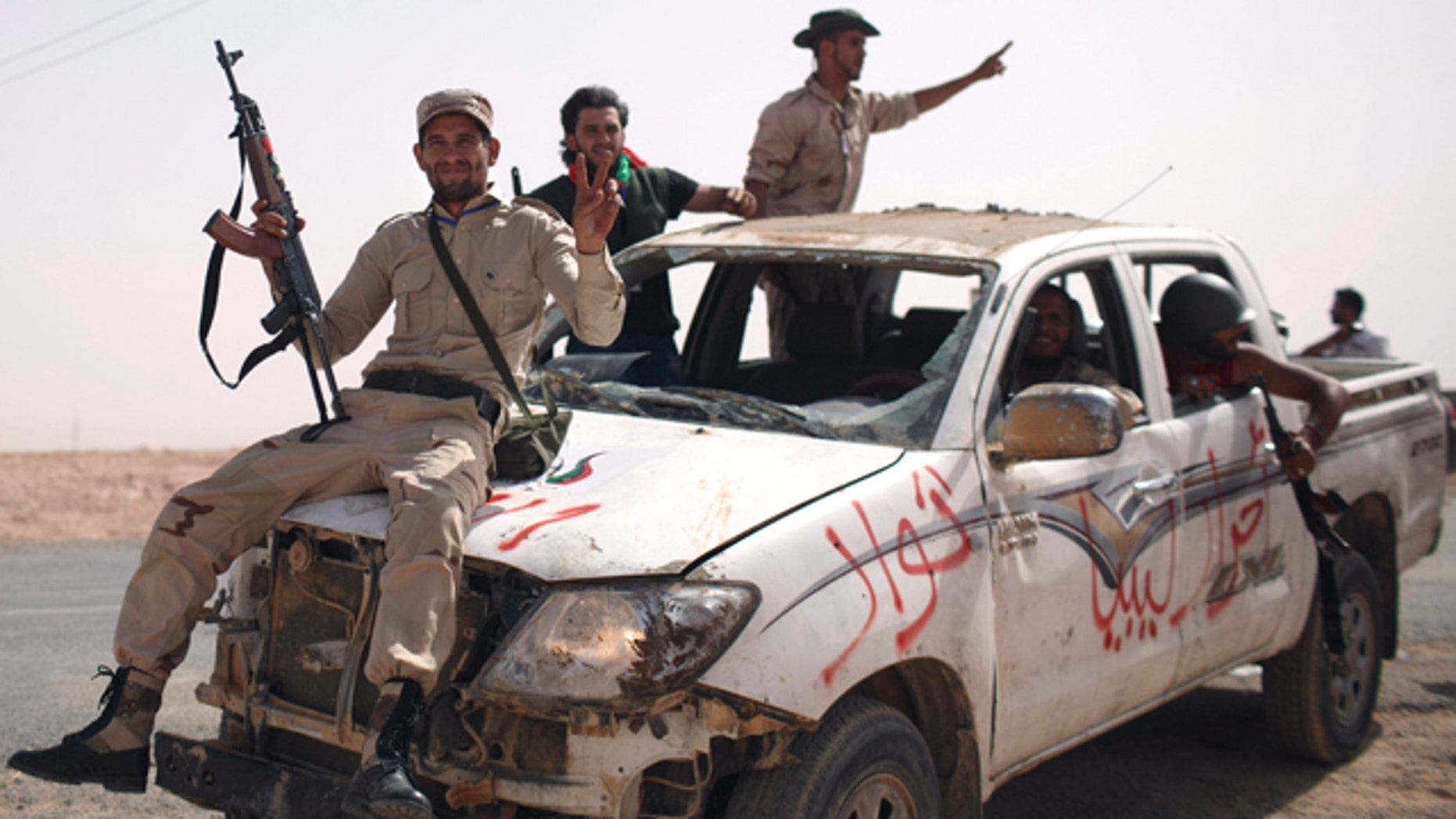 Sept. 19: Former rebel fighters arrive from inside Bani Walid with a pickup truck allegedly captured from Gadhafi loyalists, at the northern gate of the city, Libya.