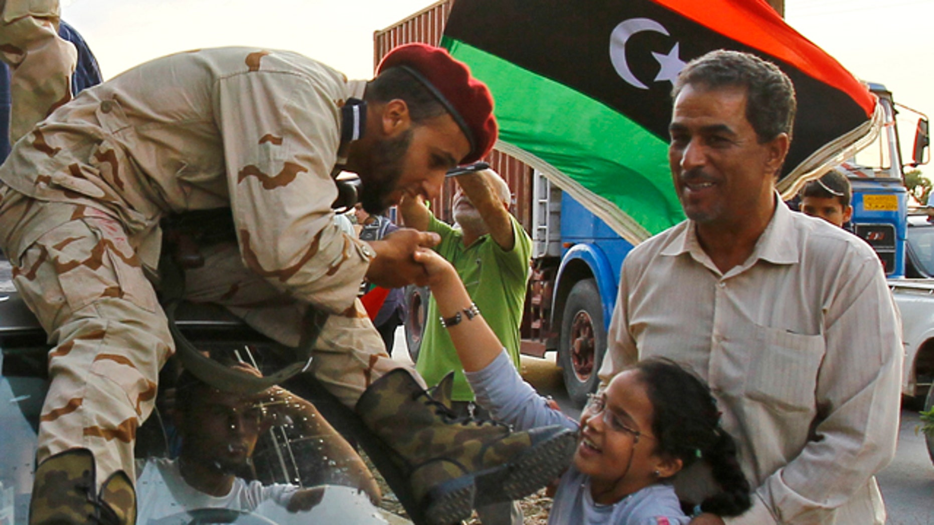 OCt. 22, 2011: A Libyan revolutionary fighter returning from Sirte is welcomed at Al Guwarsha gate in Benghazi, Libya.