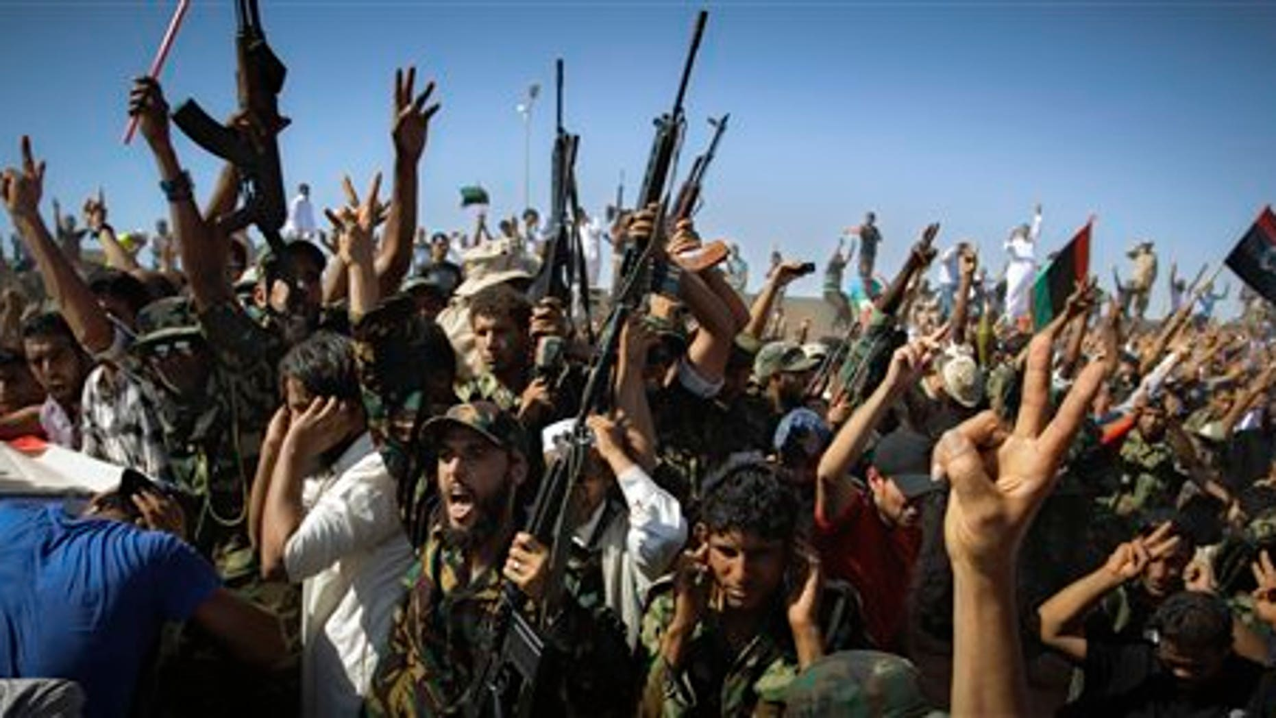 July 29: Libyan men salute and chant slogans during funeral of the Libyan rebels' slain military chief Abdel-Fattah Younis in the rebel-held town of Benghazi, Libya. Thousands of mourners marched in the funeral procession Friday for the Libyan rebels' slain military chief, a day after he was gunned down under still mysterious circumstances. Abdel-Fattah Younis was killed as he traveled from his front lines operations room to the rebels' de facto capital Benghazi.